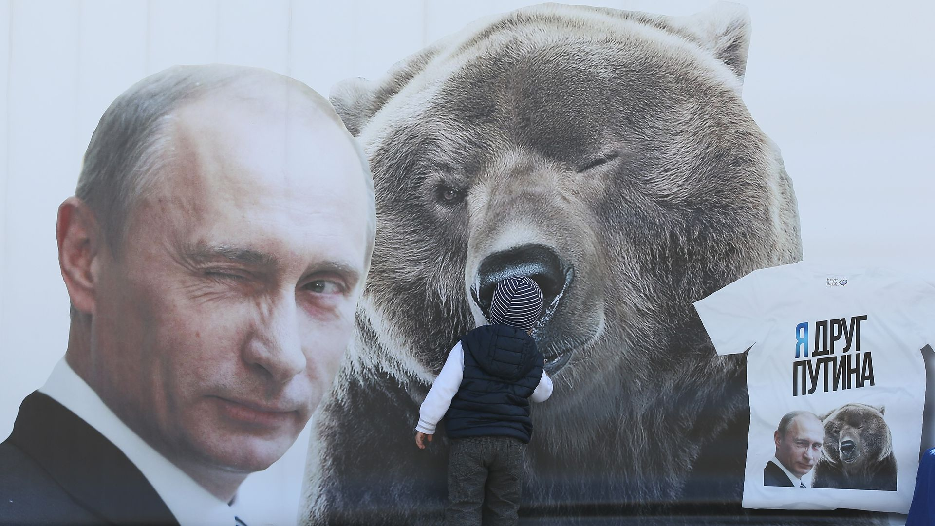 Billboard of winking Vladimir Putin next to a winking bear. They are winking different eyes.