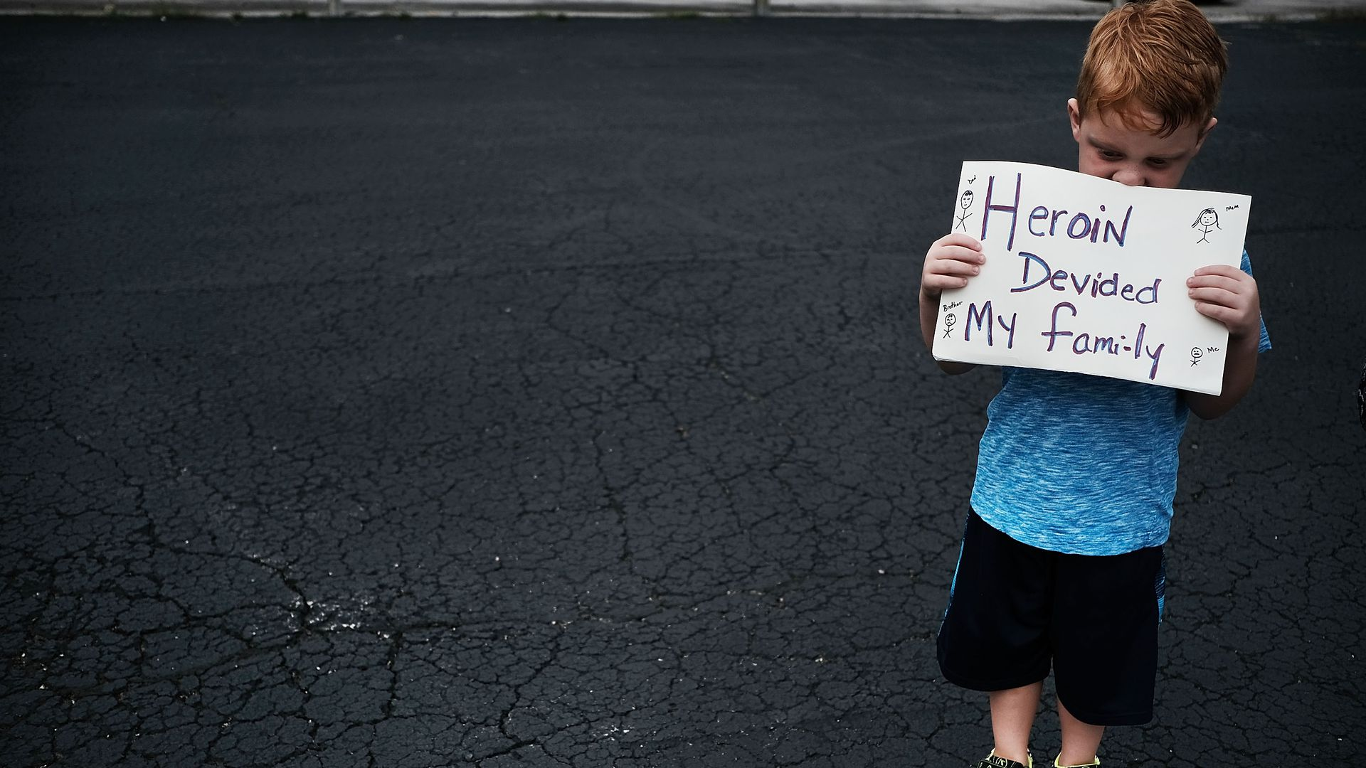 "A child holds a sign that says ""Heroin divided my family"""