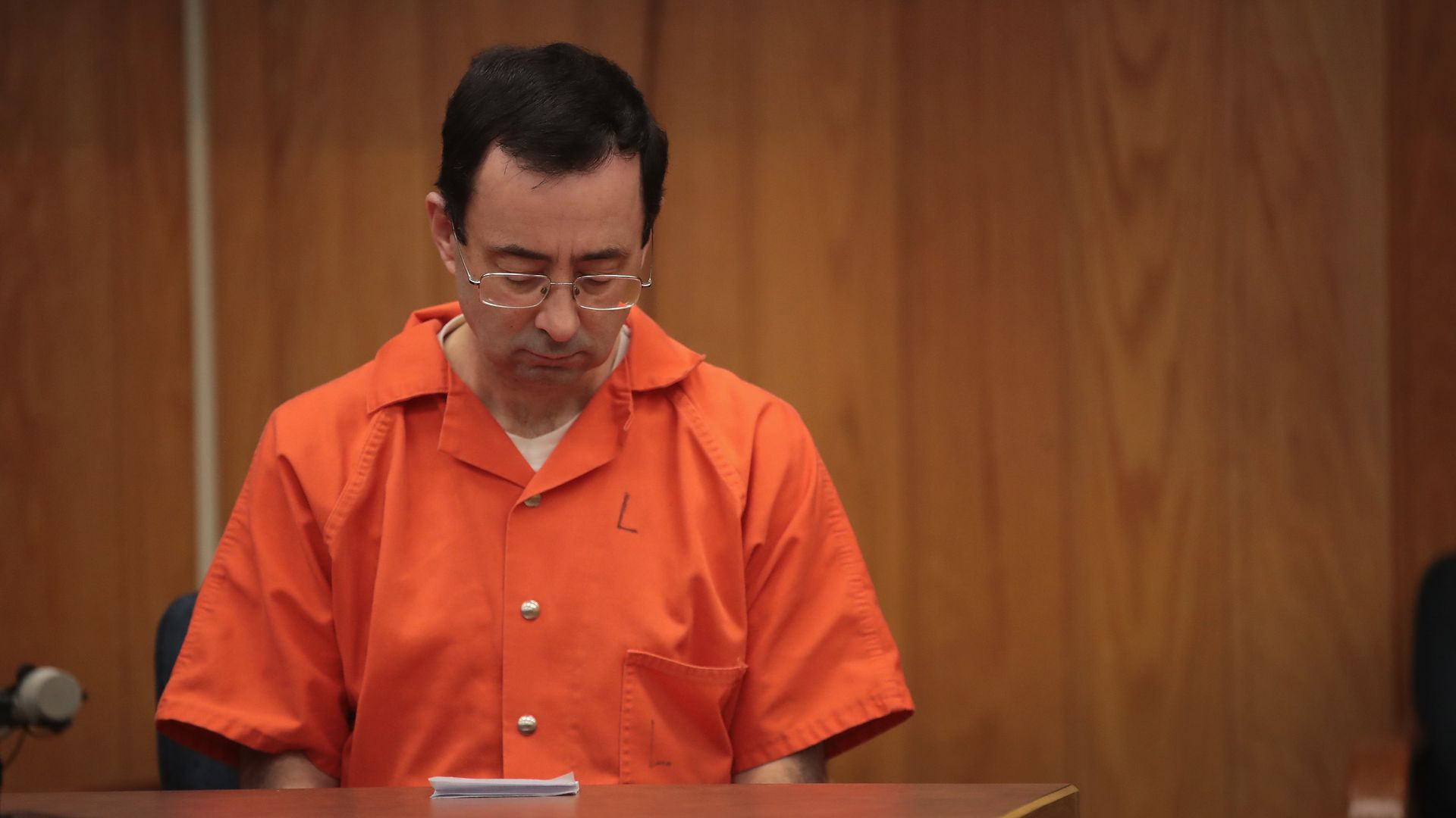 Larry Nassar, in an orange jumpsuit, looks down during his sentencing