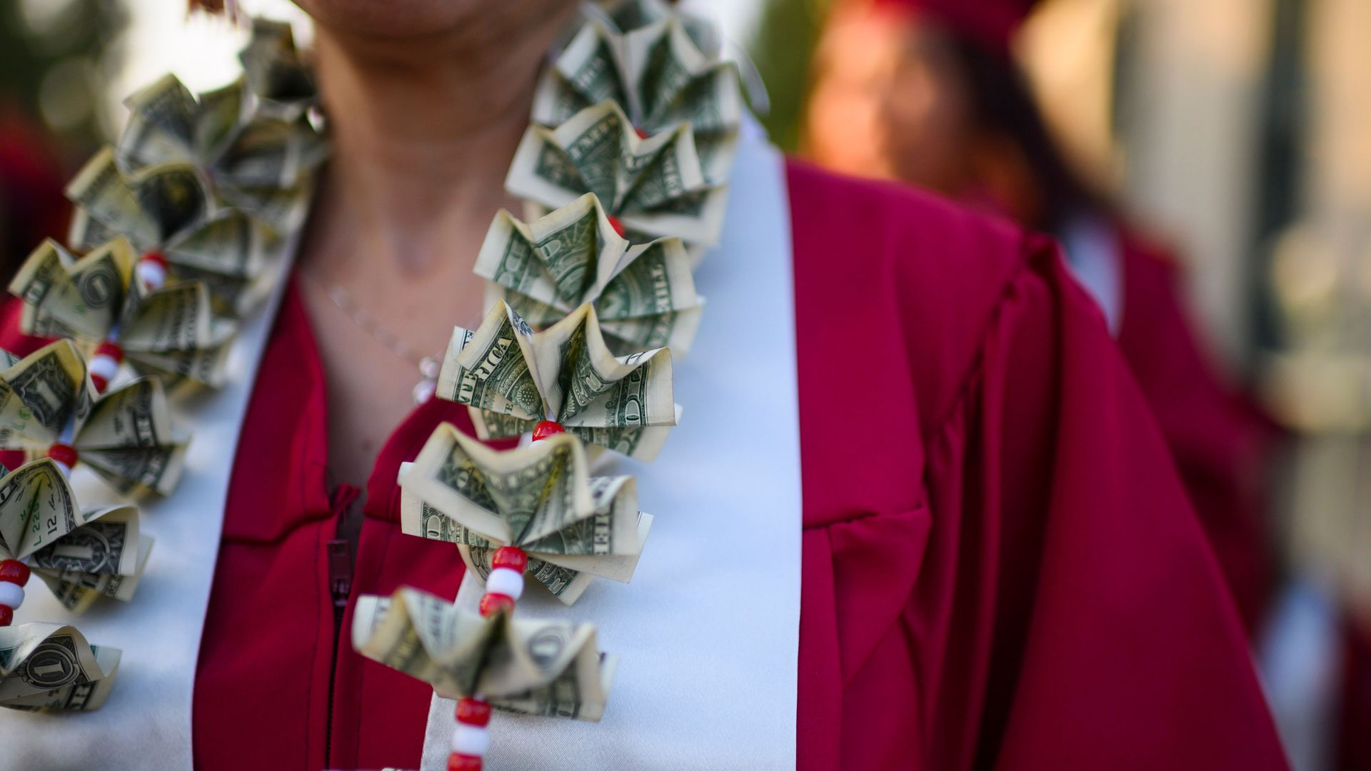 In this image, a woman wears a gown with a sash and folded dollar bills.