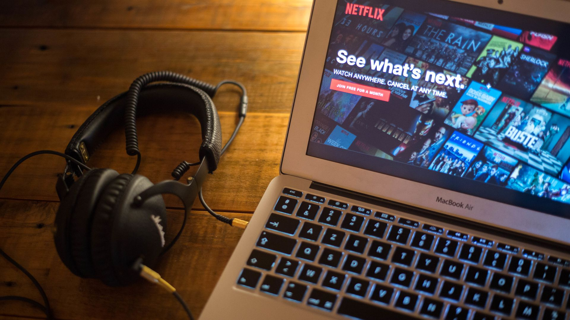 A pair of headphones next to a laptop, with the Netflix homepage pulled up.
