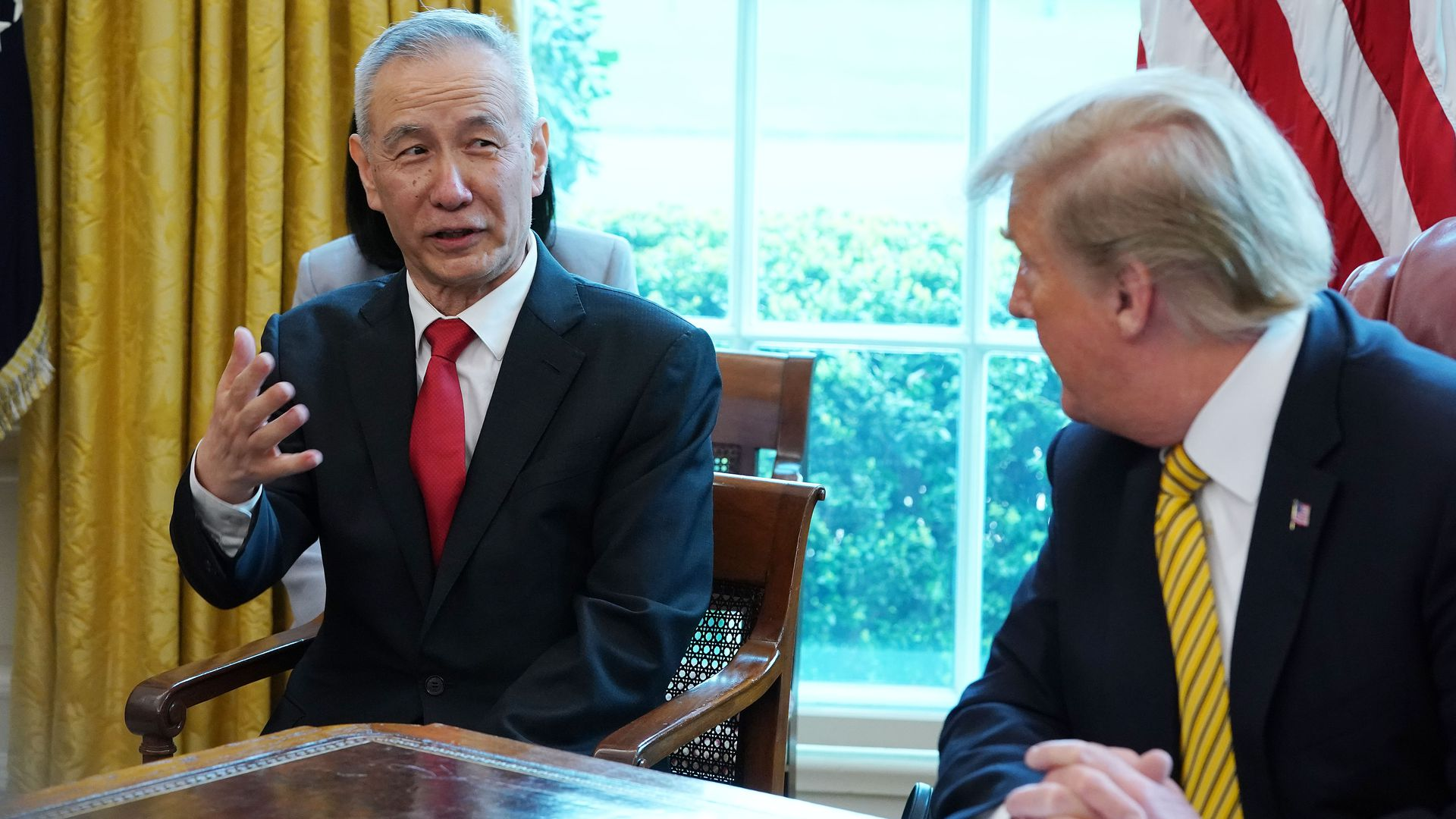 In this image, Trump sits at his desk in the Oval Office and listens to Liu He.