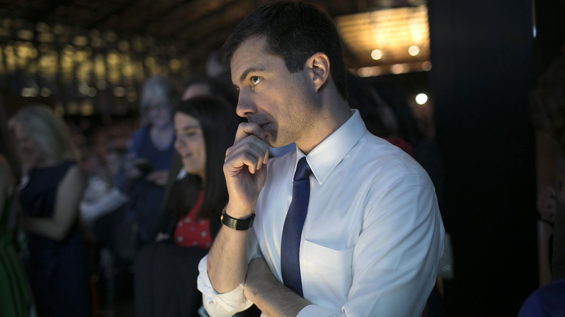 Pete Buttigieg standing with his hand over his mouth.