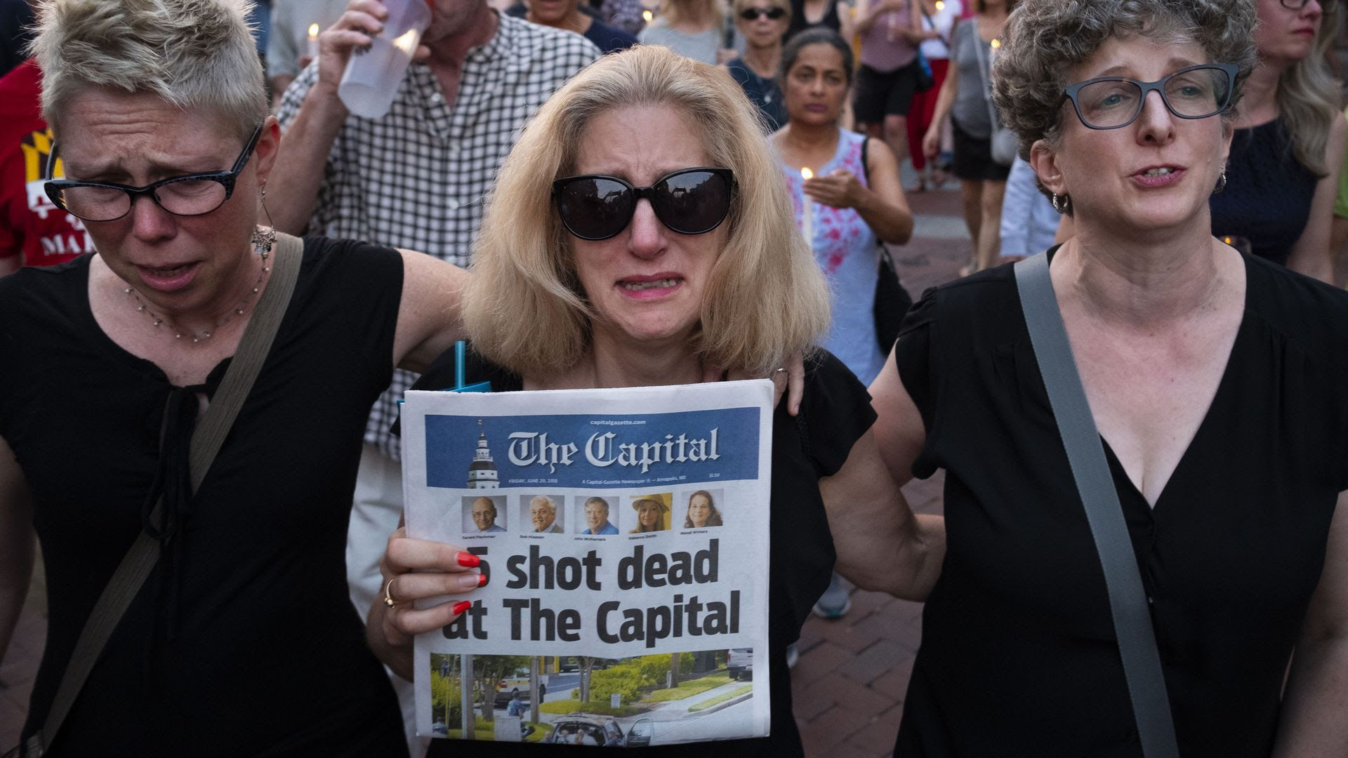 A woman holds a newspaper showing deaths at a newsroom in Maryland.