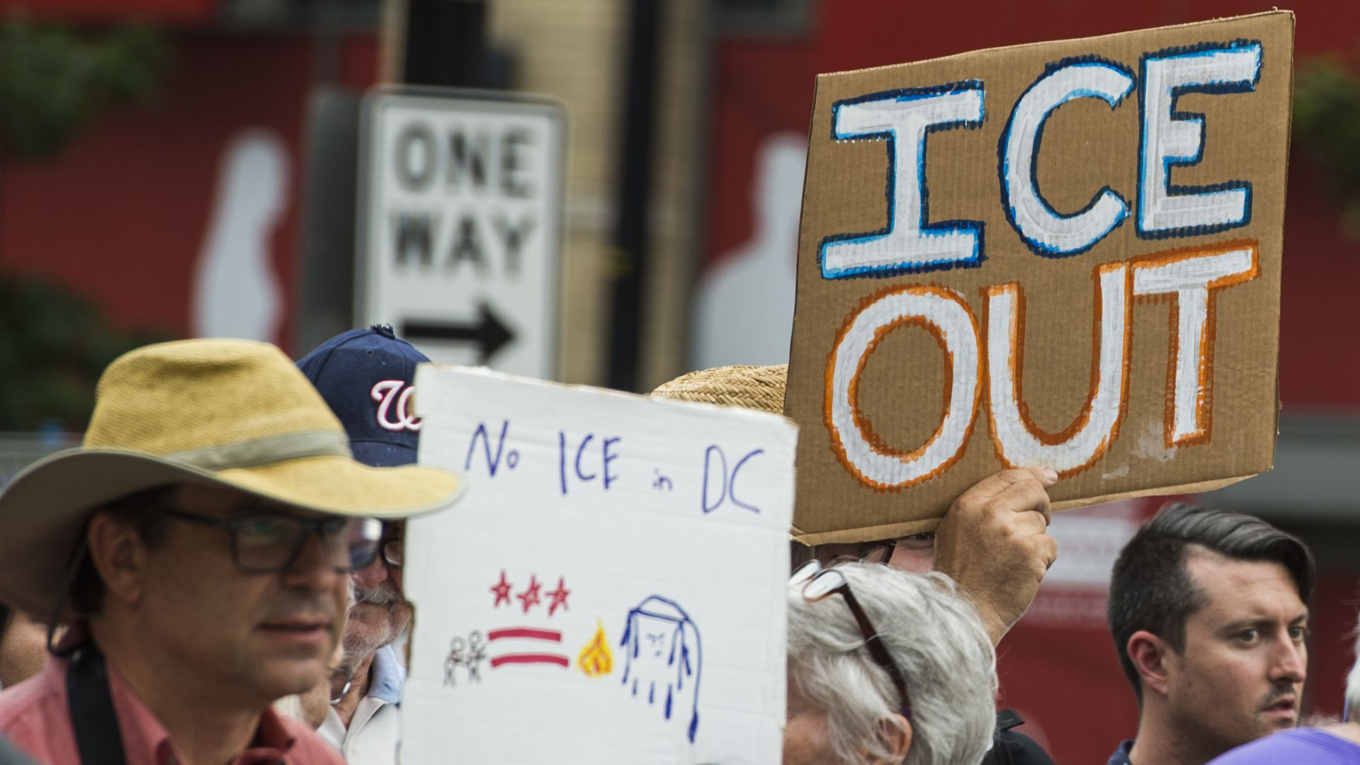 "This image shows someone holding a sign that reads ""ICE OUT"" in a crowd."