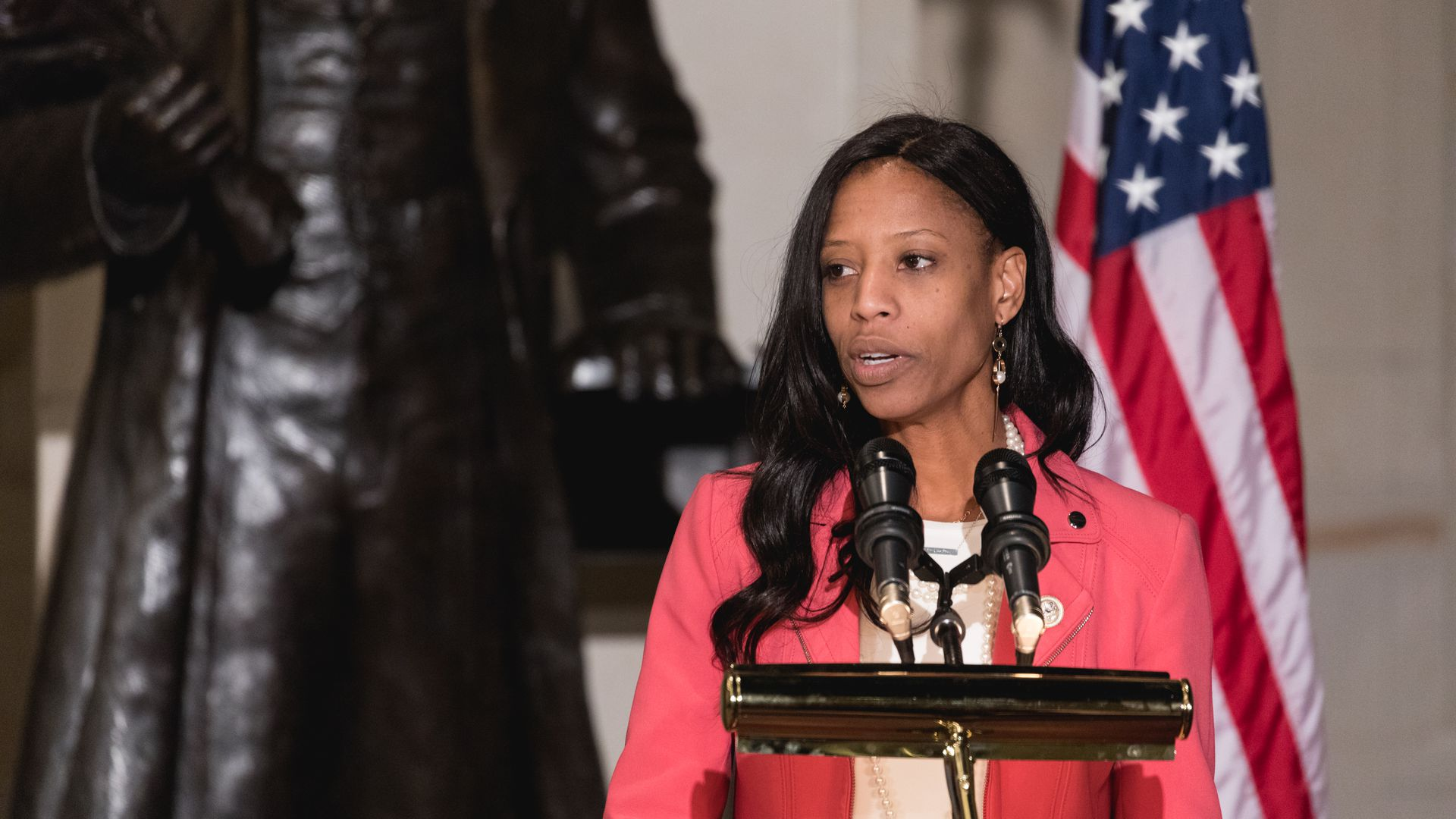 Mia Love before an American flag at a podium speaks.