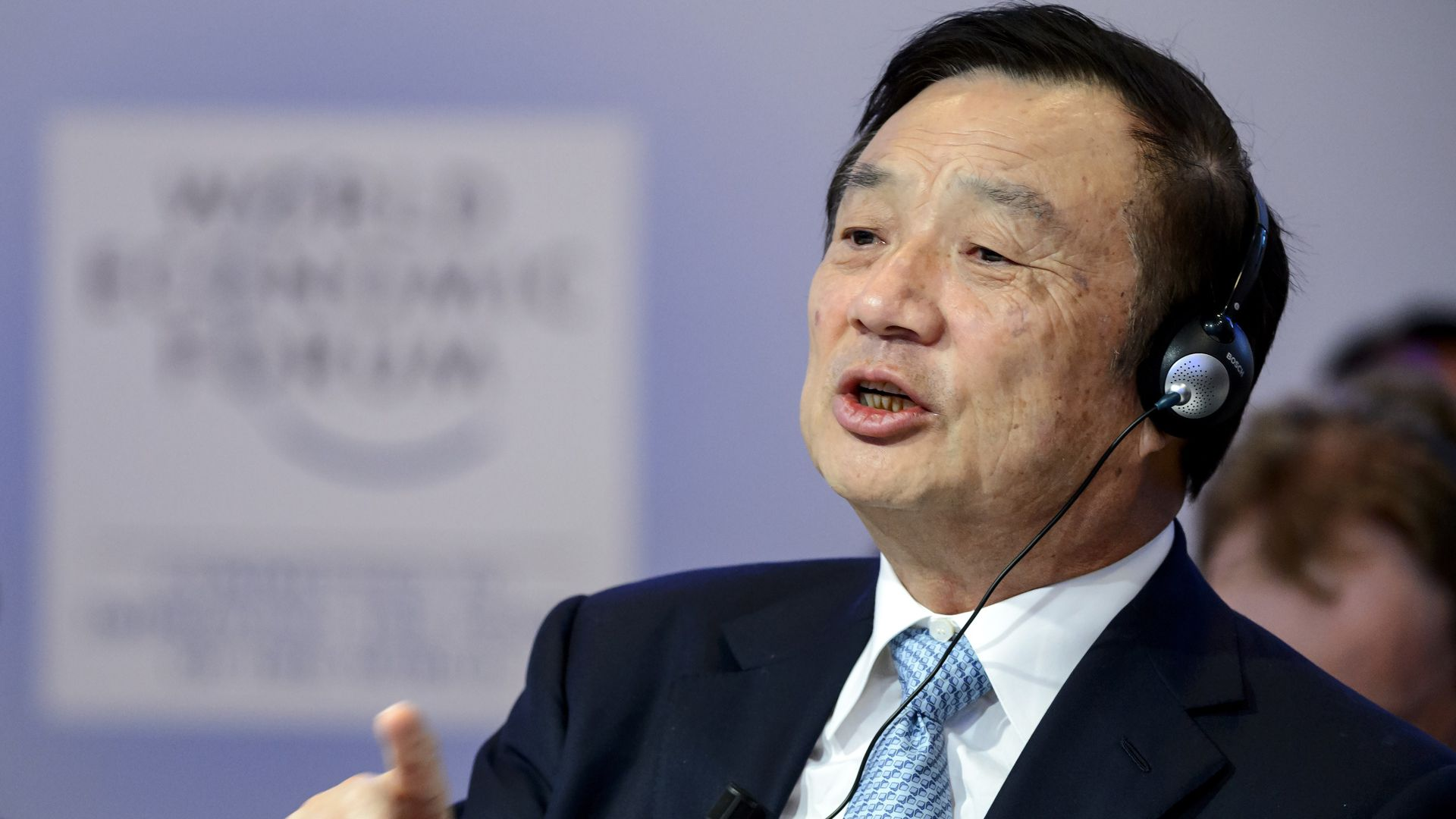 Huawei founder with translation headset on