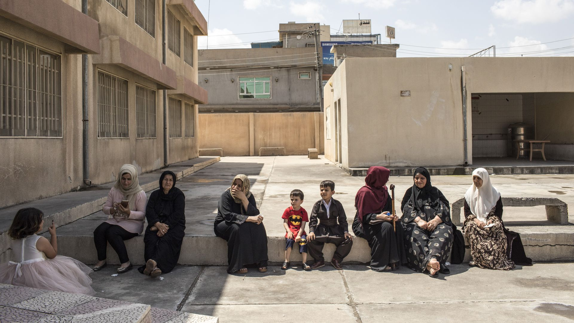 Women and children sit on a curb next to a building