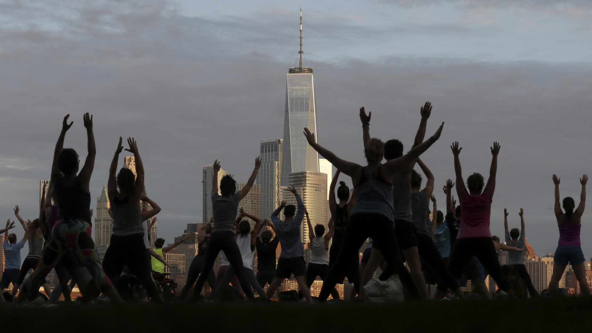 Silhouettes of people doing a yoga on a pier facing Lower Manhattan