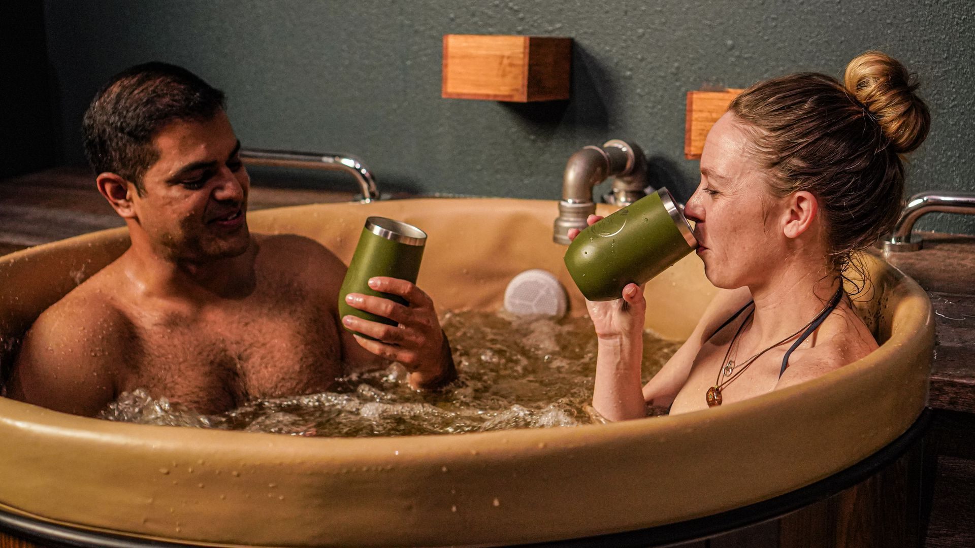 Picture of two people in a bath tub filled with water that smells similar to beer
