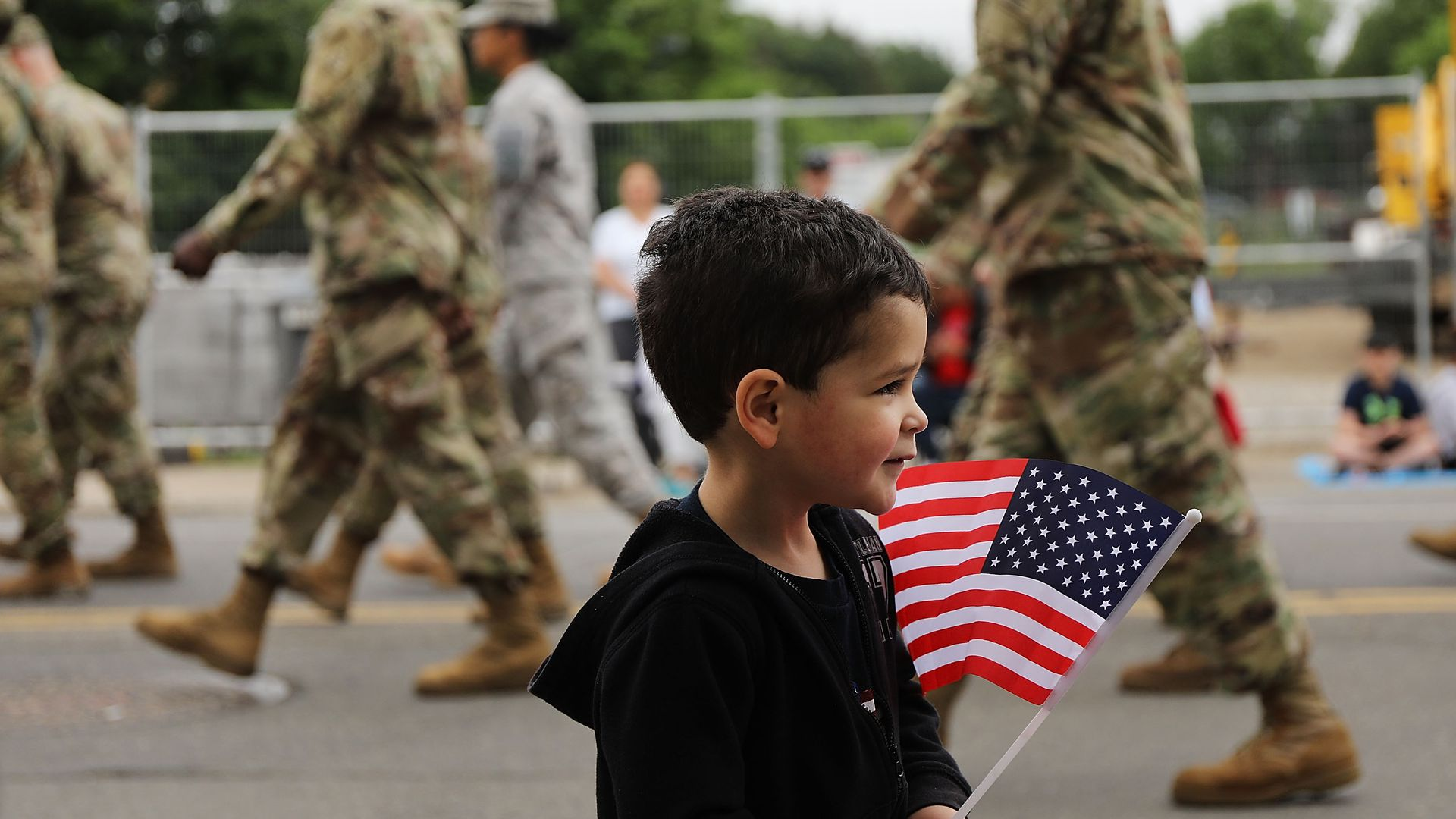 A child holding an American flag while U.S. soldiers walk by.
