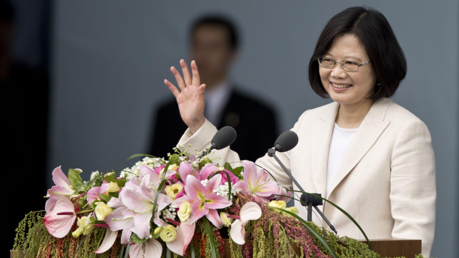 Taiwanese president Tsai Ing-wen waving from behind a lectern