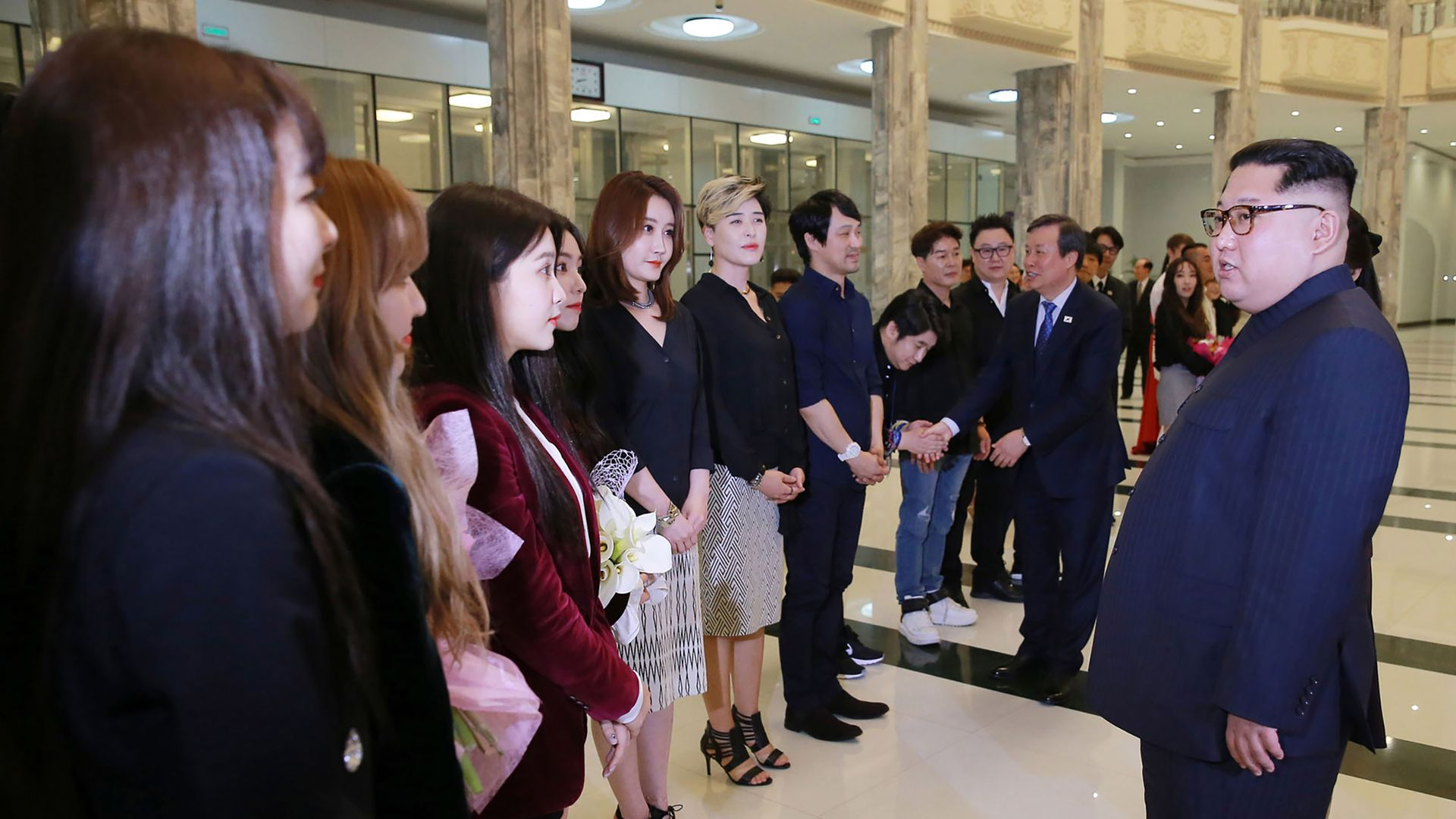 Kim Jong-un (right) speaks with South Korean performers (left) in Pyongyang.