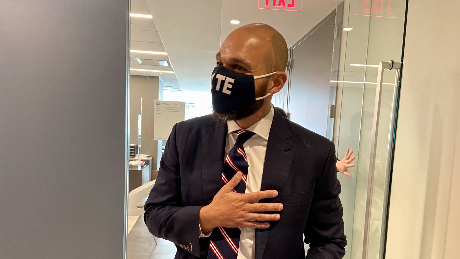 """Robert White exits the Office of Campaign Finance after filing to run for mayor, wearing a """"vote"""" face mask."""