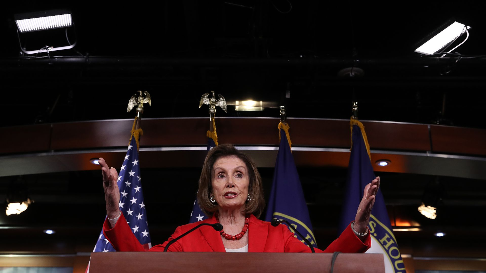 In this image, Nancy Pelosi stands behind a podium and speaks.