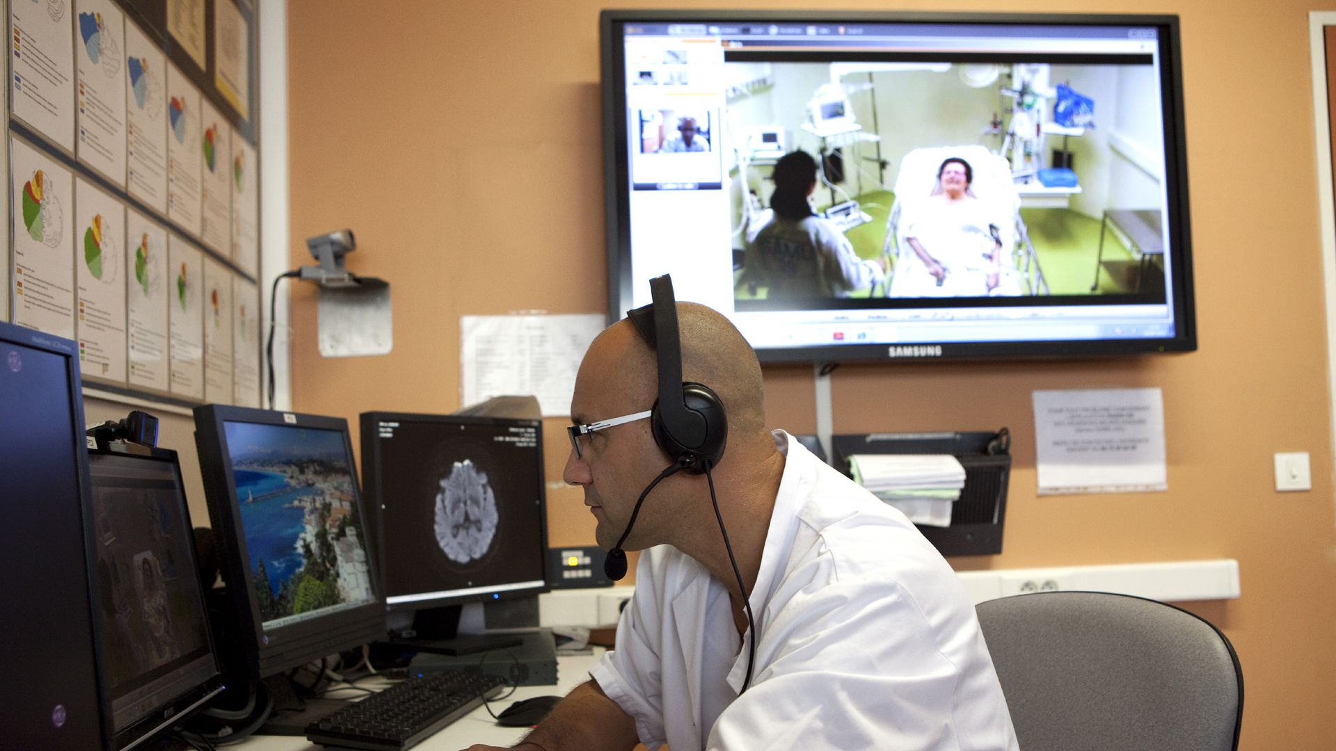 A man sits behind computers during a telehealth consultation with a patient.