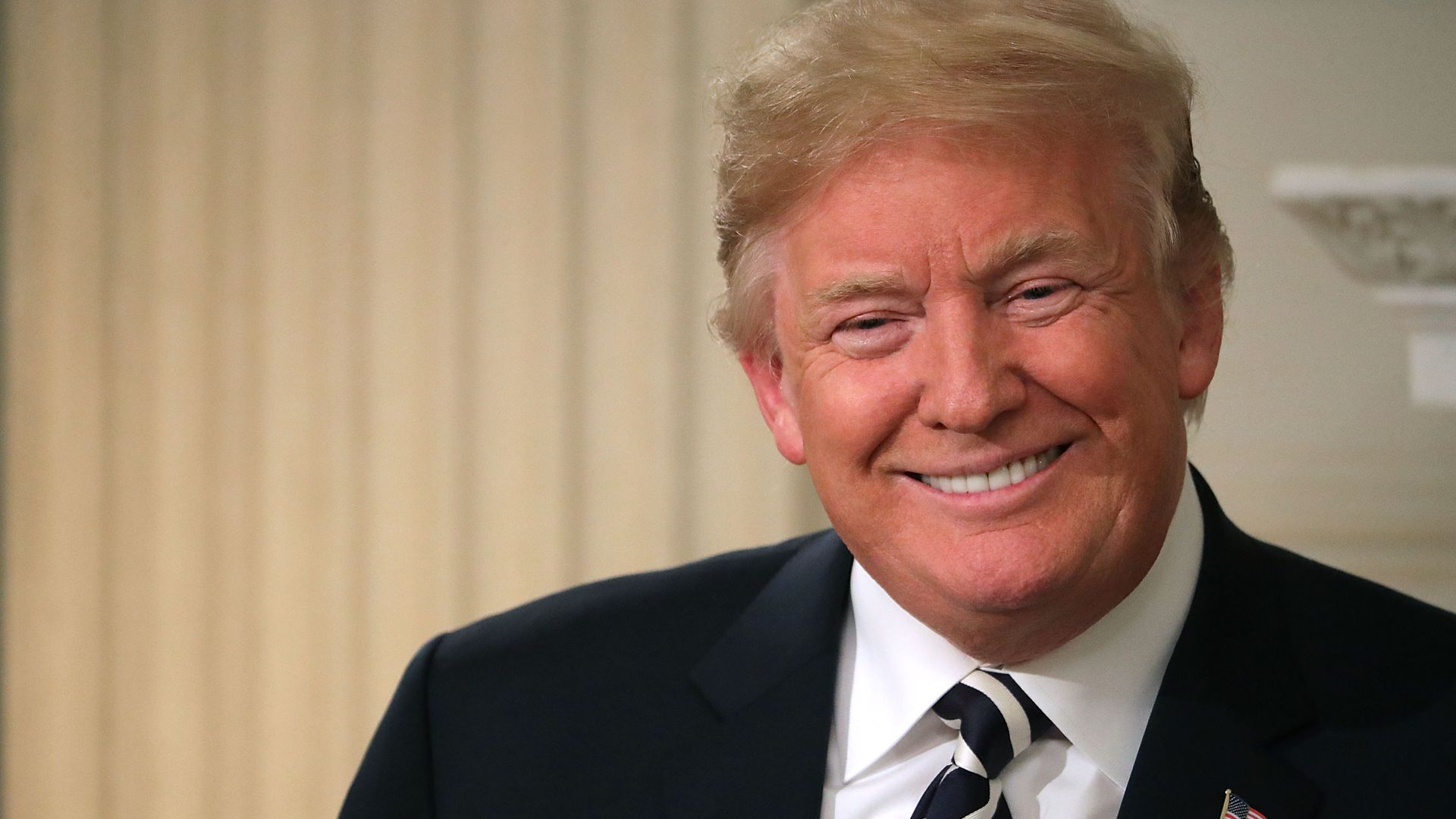 Trump smiles in a black suit before a white background.