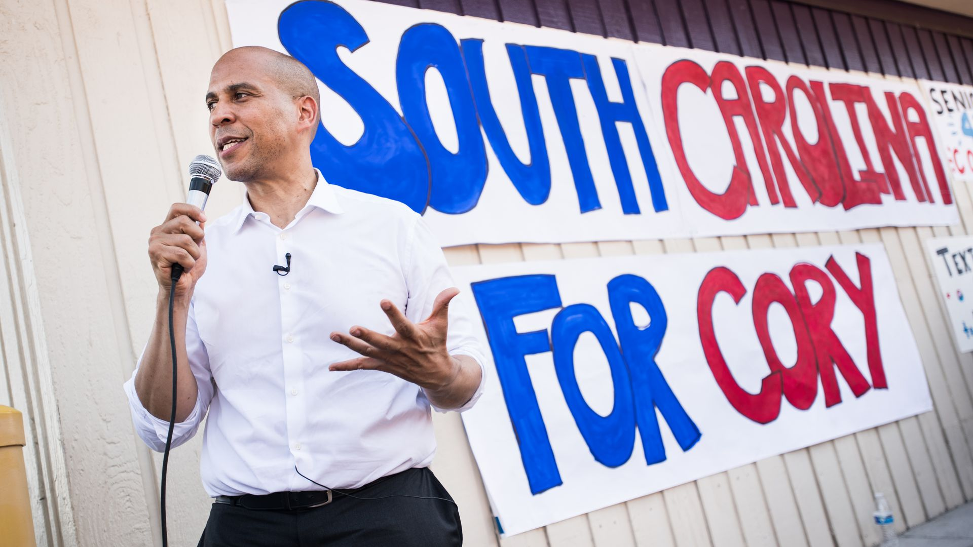"Cory Booker holds a microphone and stands in front of a sign that says ""South Carolina for Cory."""