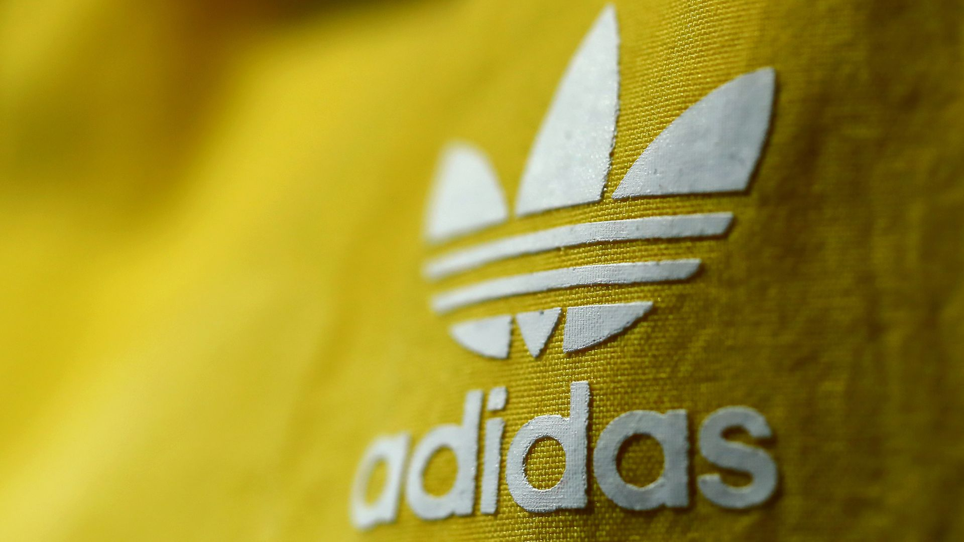 Adidas logo in white on yellow cloth.