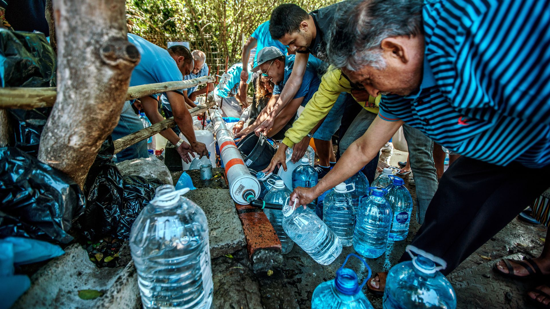 Cape Town residents filling water jugs from pipe