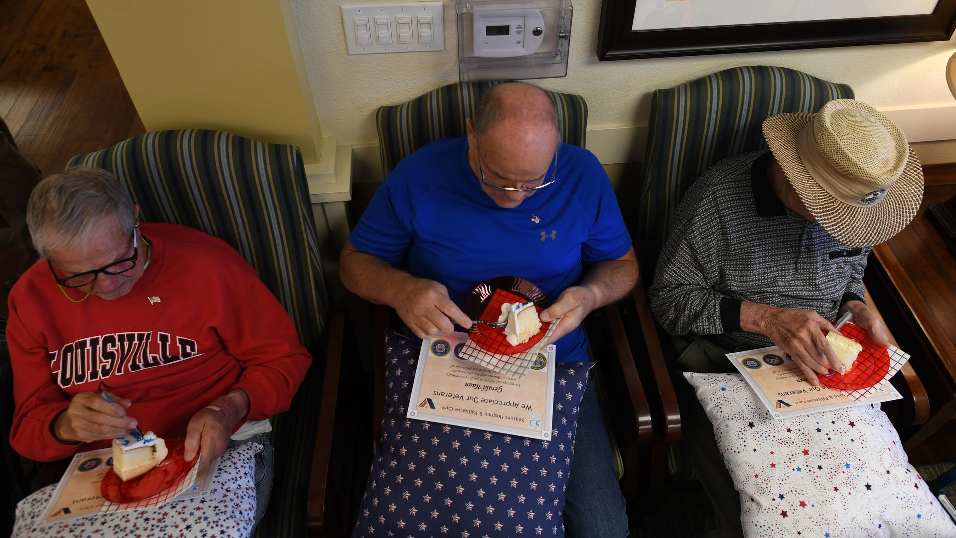 In this image, three seniors sit and eat cake. A few have blankets over their laps.
