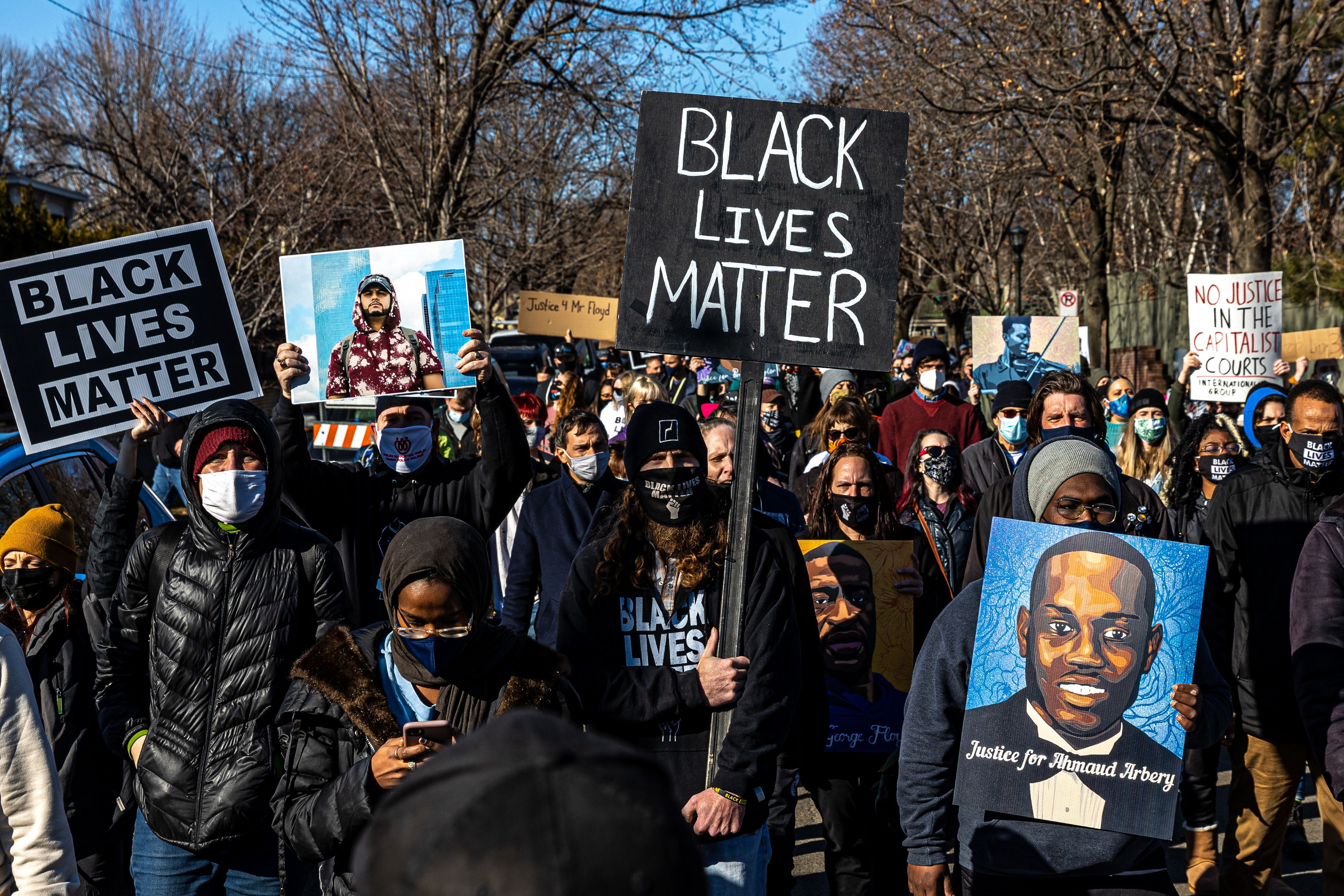 Demonstrators march while holding placards during a protest in St.Paul, Minnesota, on March 6