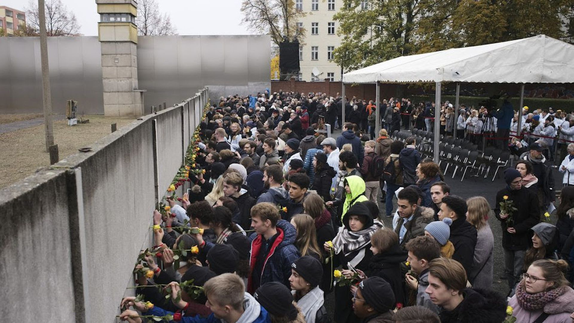 Young people stick flowers in remains of the Berlin Wall during a commemoration ceremony today