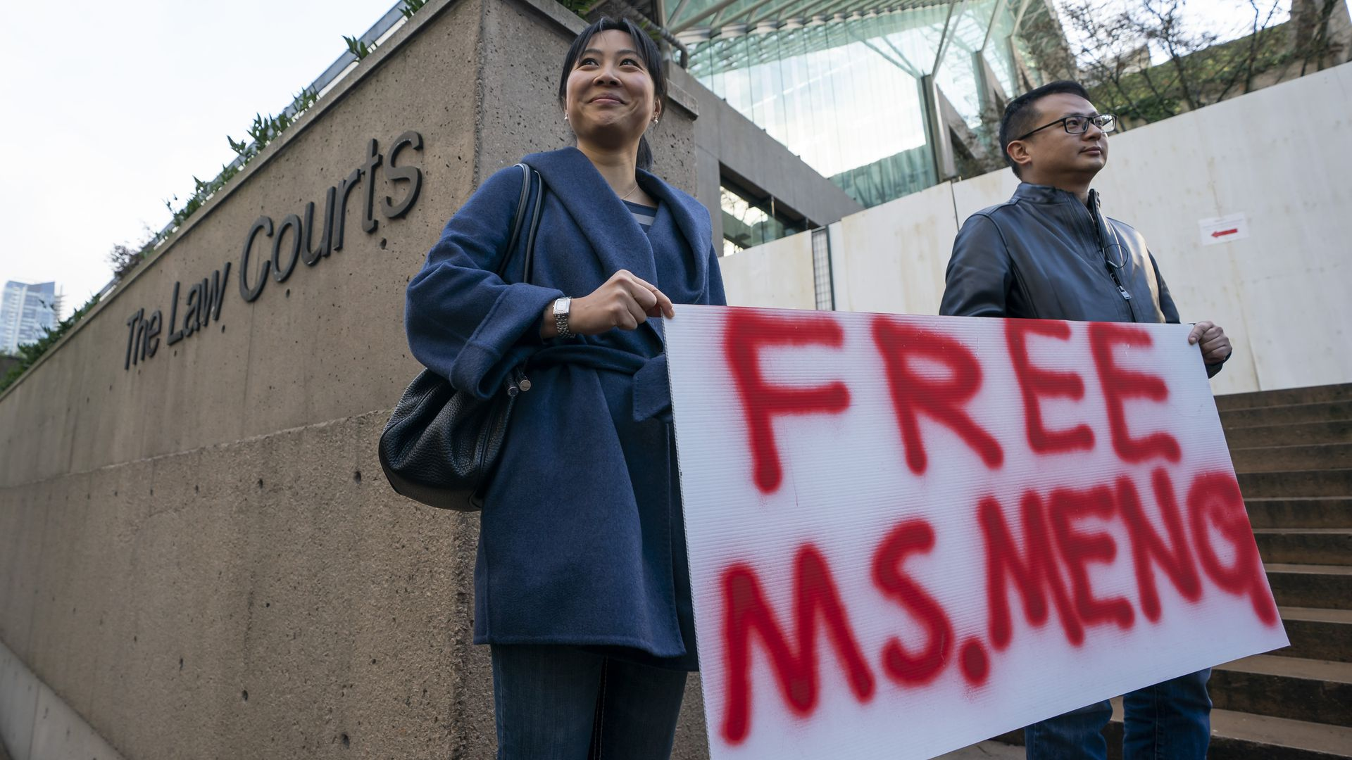 """Protesters carrying sign reading """"Free Ms. Meng"""" outside courthouse"""