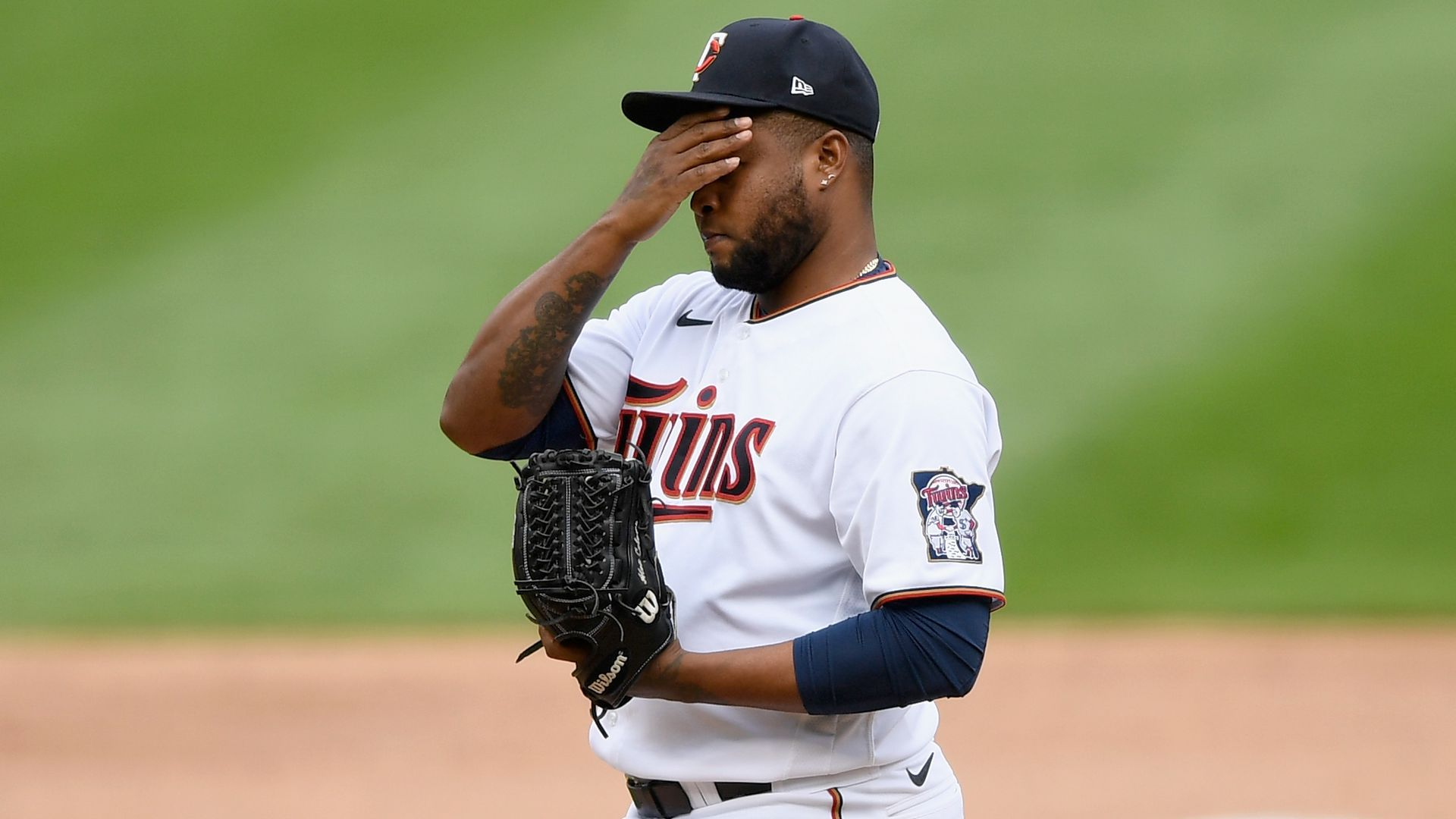 A baseball player puts his hand over his face