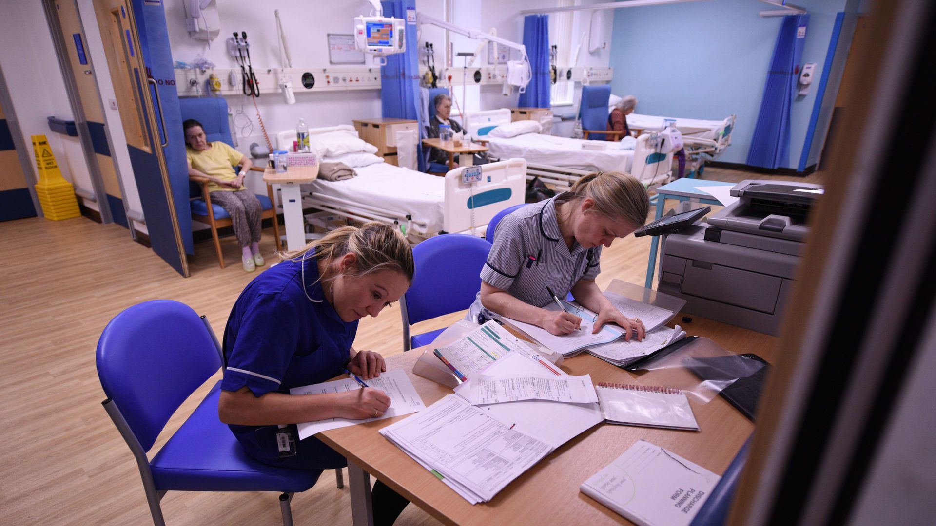 Nurses writing on papers near hospital beds