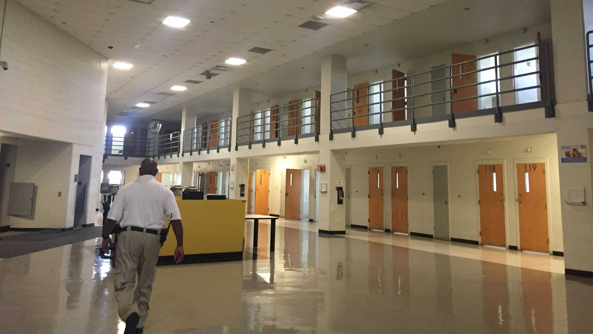A city jail employee walks in the empty open-plan floor with individual cells along the side of the room.