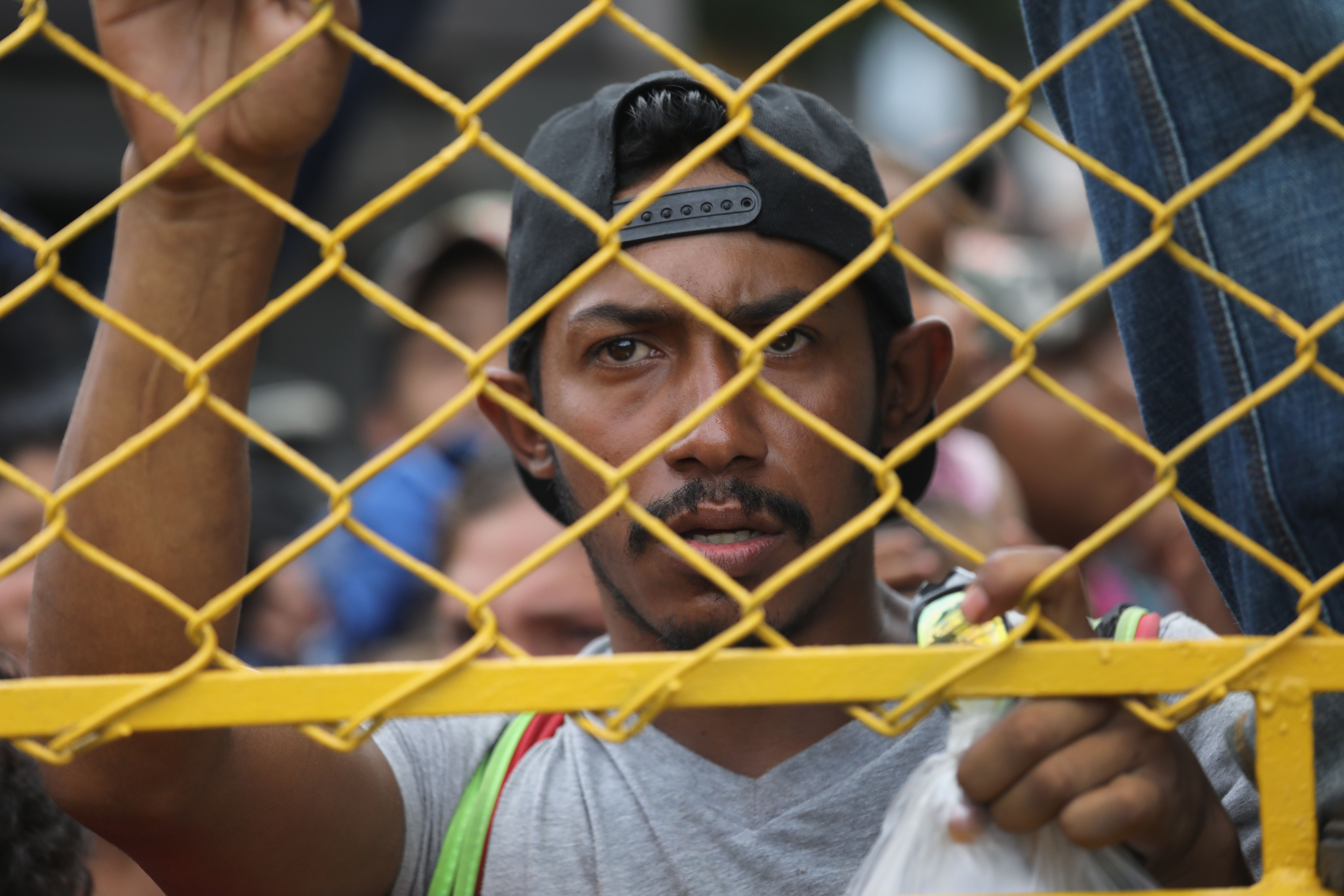 A migrant at the gate separating Guatemala and Mexico