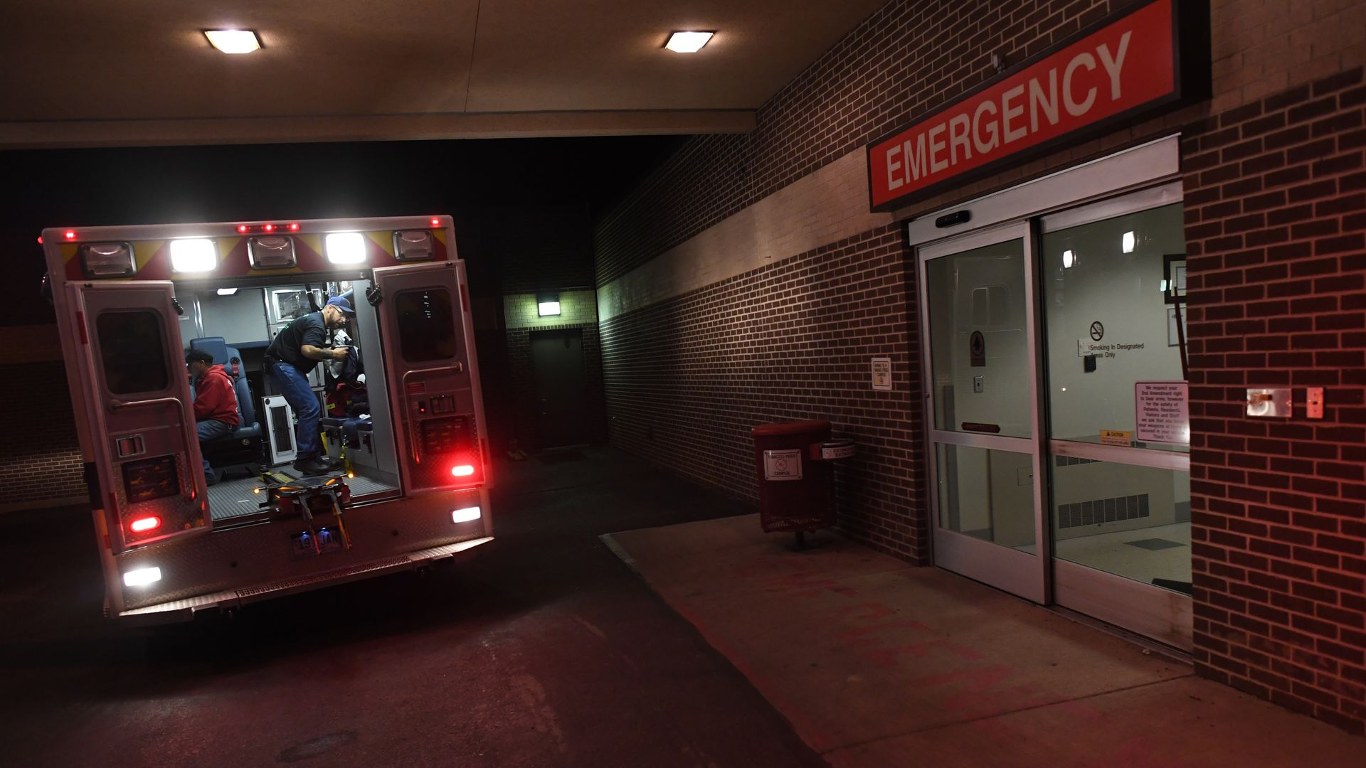 An ambulance is parked outside of a hospital emergency department.