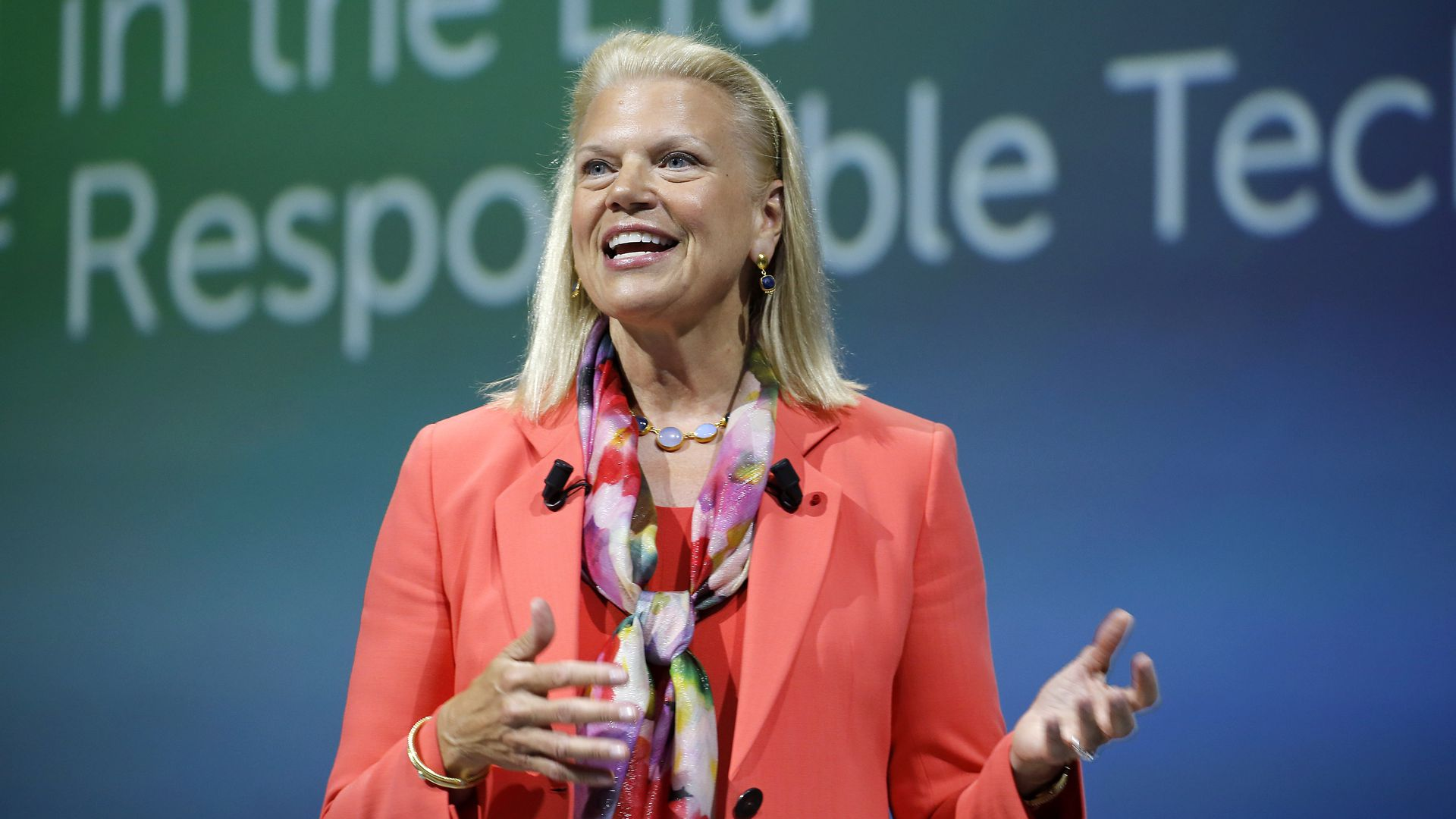 Ginni Rometty is a red jacket presents on stage