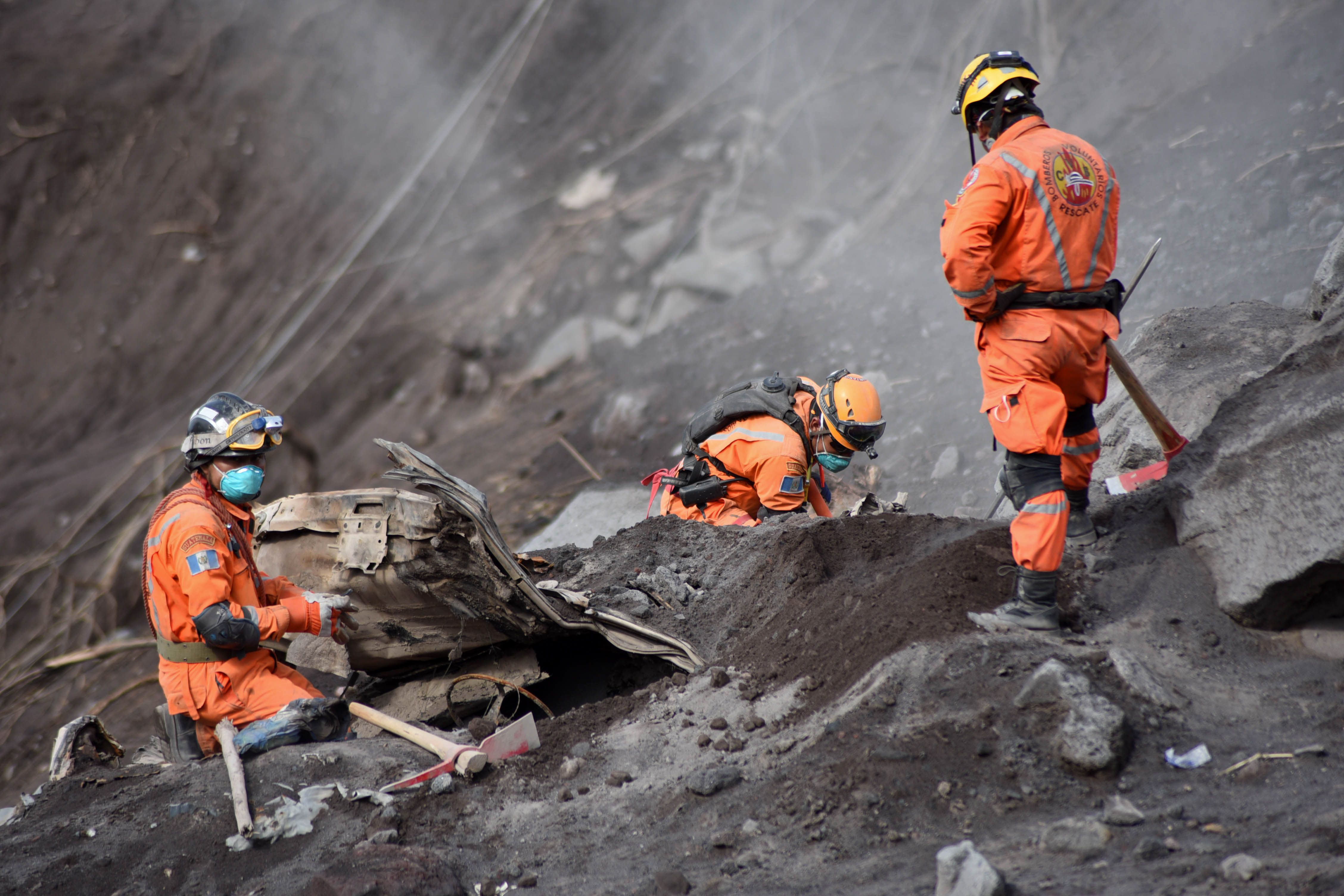 Volunteer firefighters search for victims of Sunday's Fuego Volcano eruption