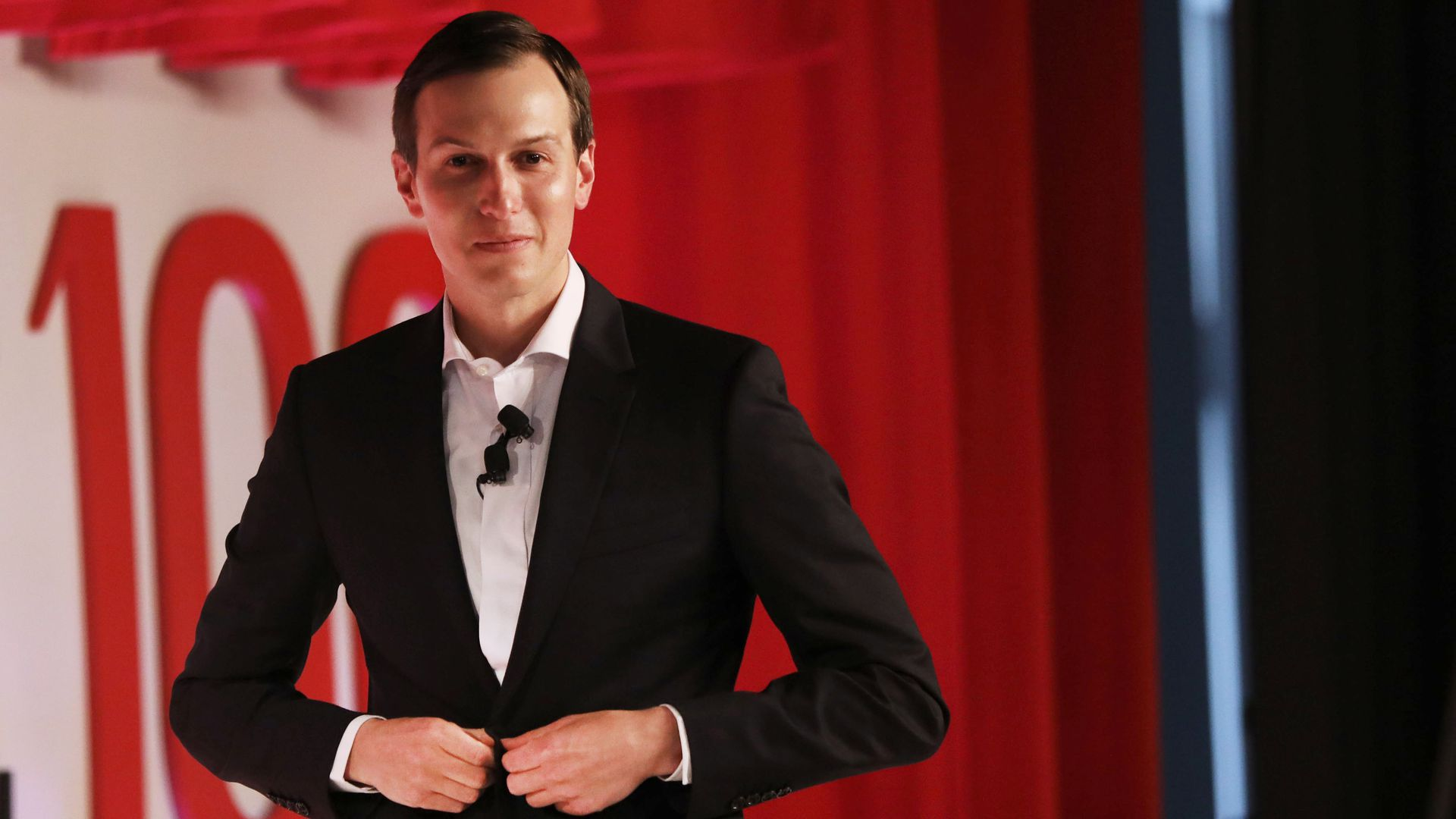 Jared Kushner walking off of a stage at an event while buttoning his blazer.