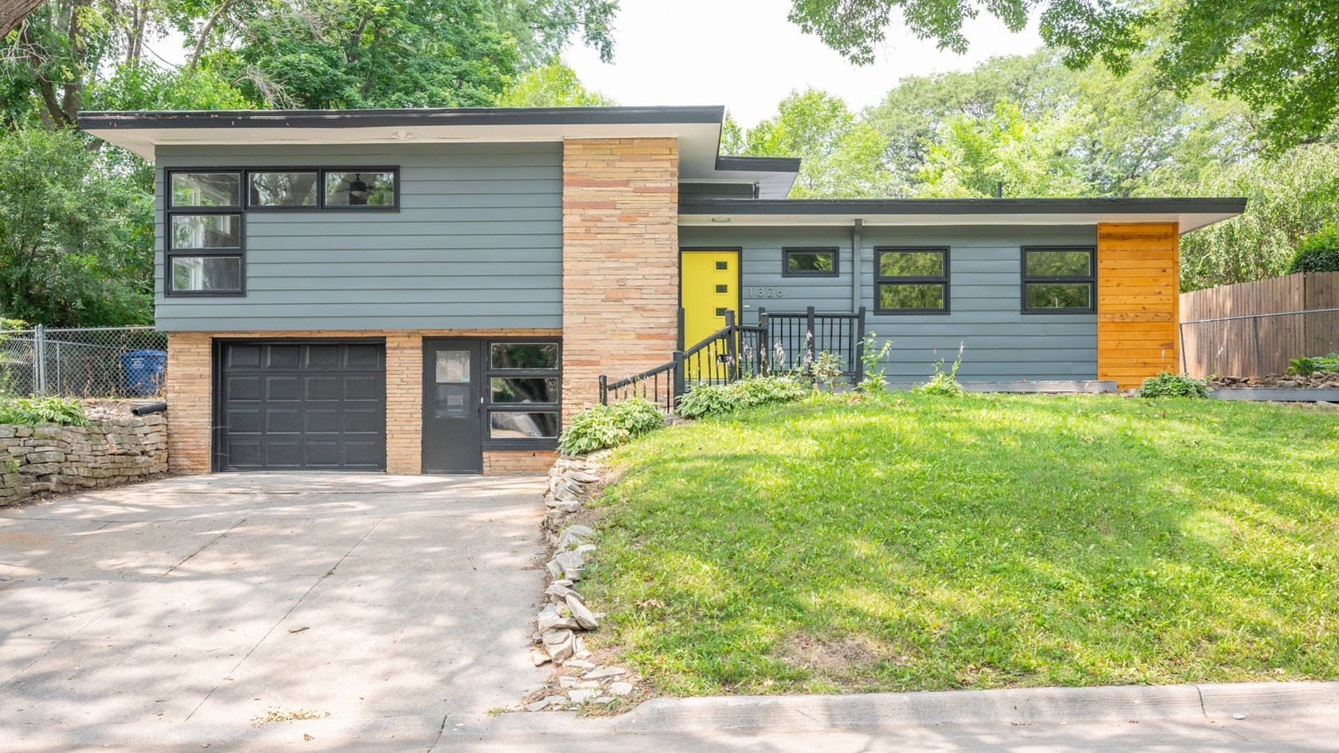 A mid-modern split-level home for sale is Des Moines with a yellow front door.