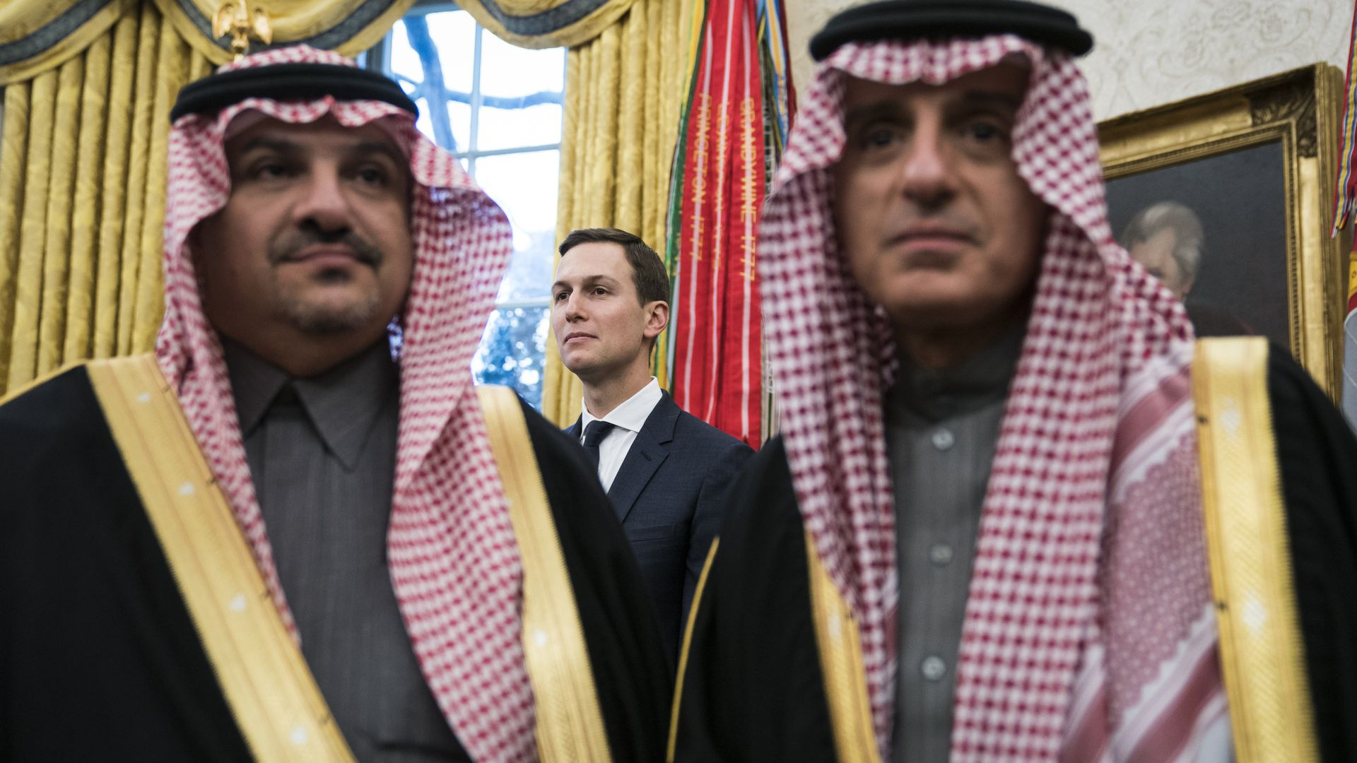 Jared Kushner stands behind two Saudi men.