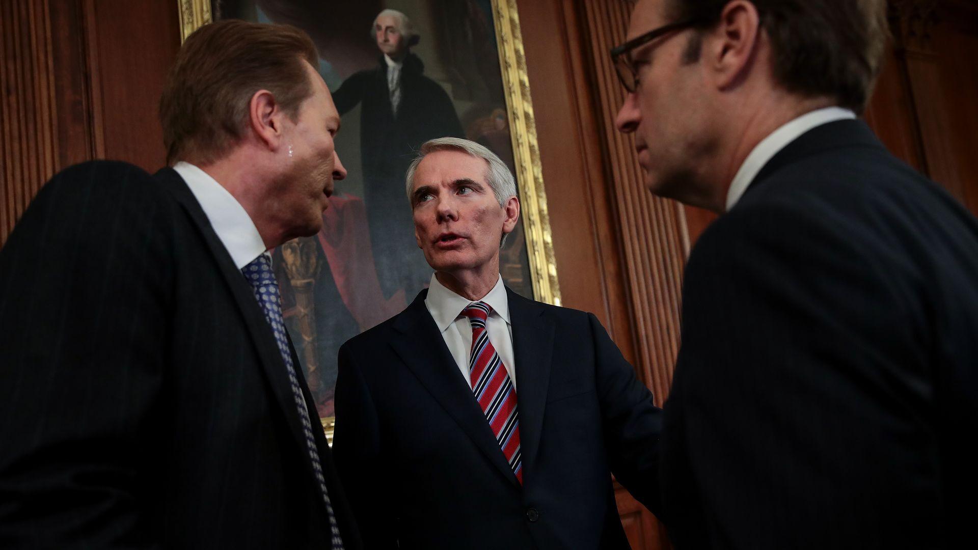 Senator Rob Portman speaks with two men
