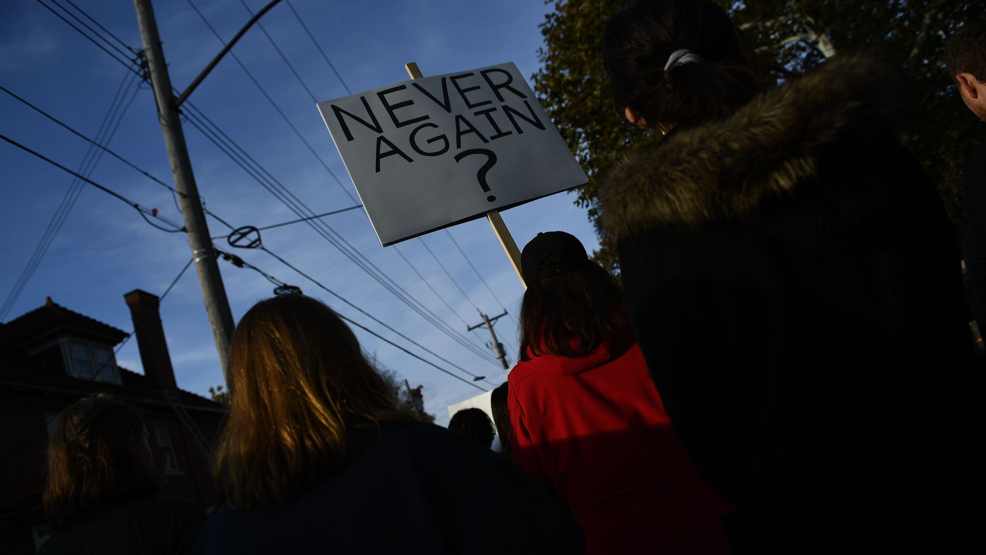 "A shadowy image of a few women marching in front of the camera carrying a sign that says, ""Never again?"""