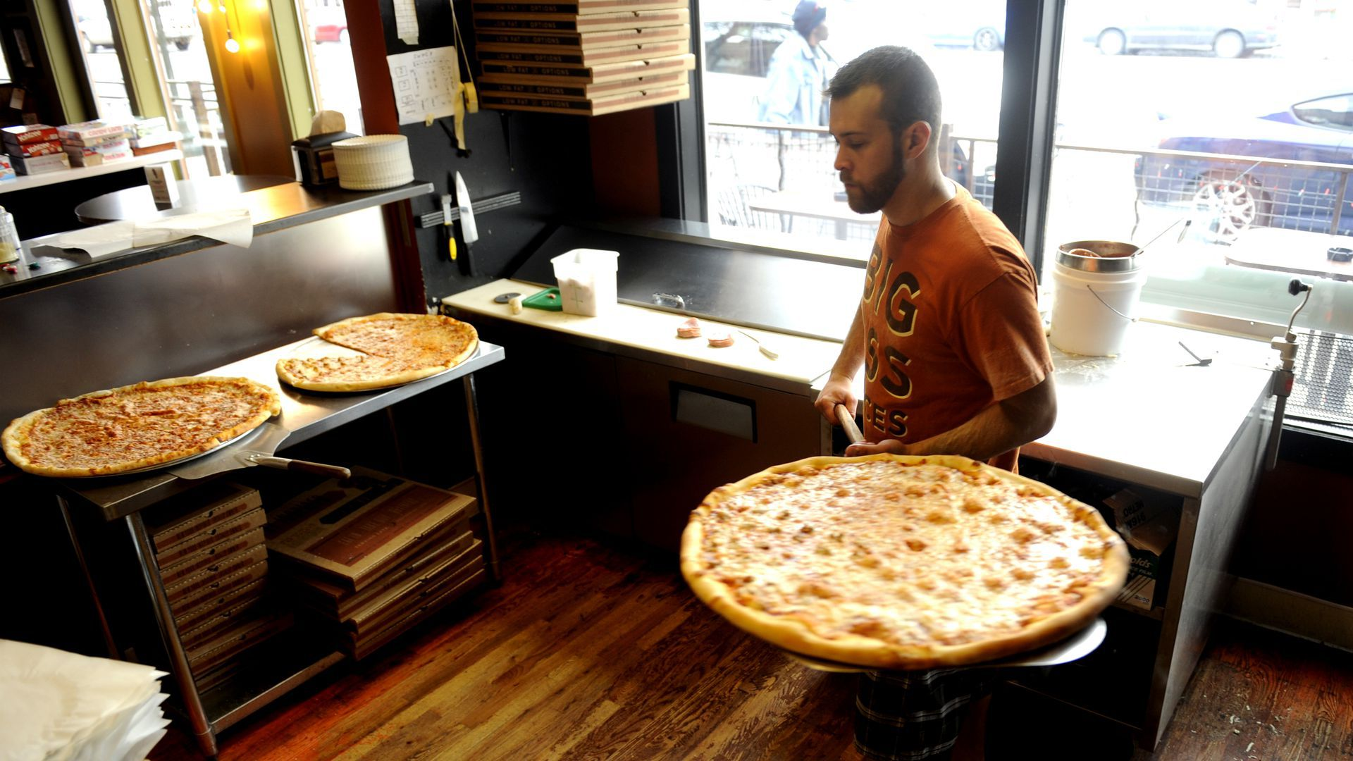 An employee carries a large pizza