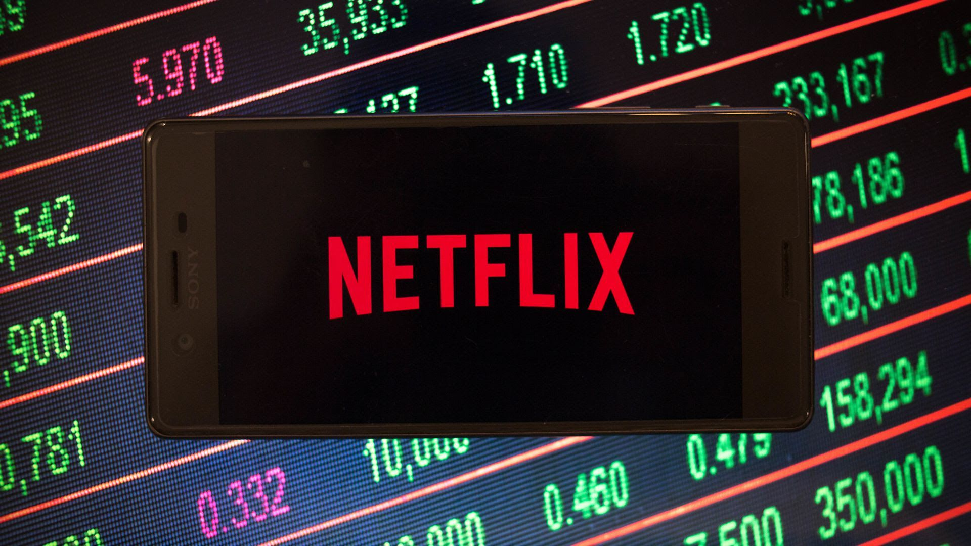 An illustration of the Netflix logo on a phone, set against a screen of numbers from the stock market