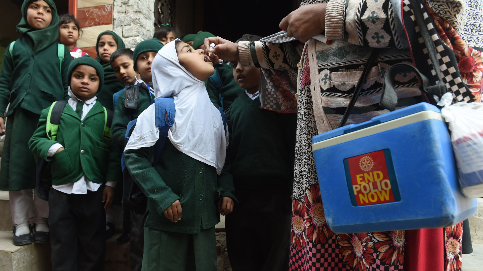 A Pakistani health worker administers polio vaccine drops to school children during a polio campaign.
