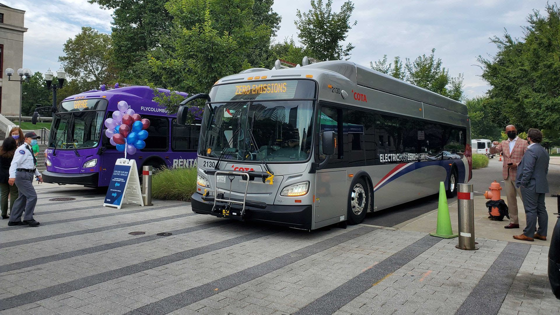 Two electric buses are seen Wednesday morning outside of Columbus City Hall. The COTA bus on the right will begin carrying passengers next week.
