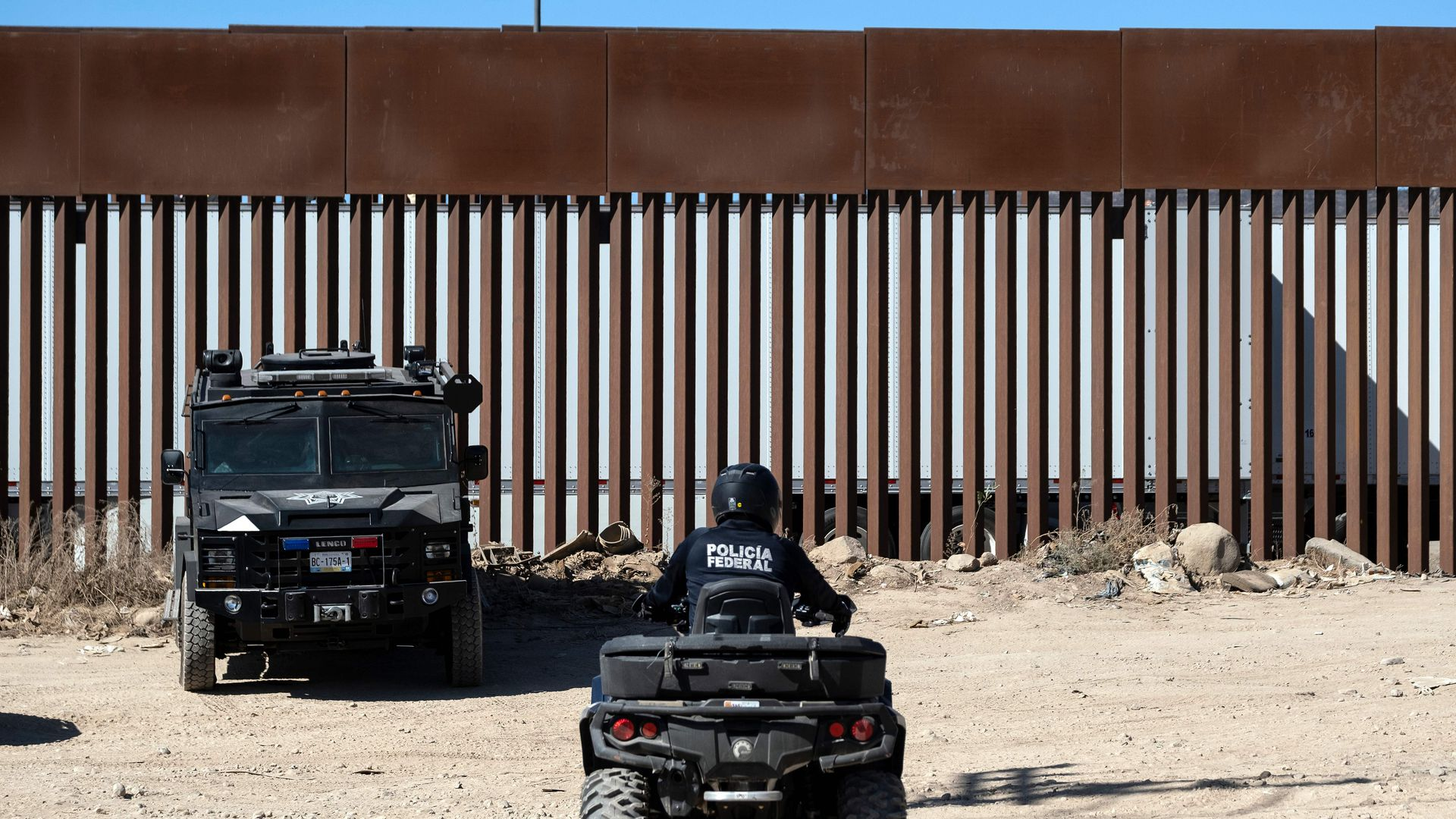 In this image, police sit in cars next to the border wall.