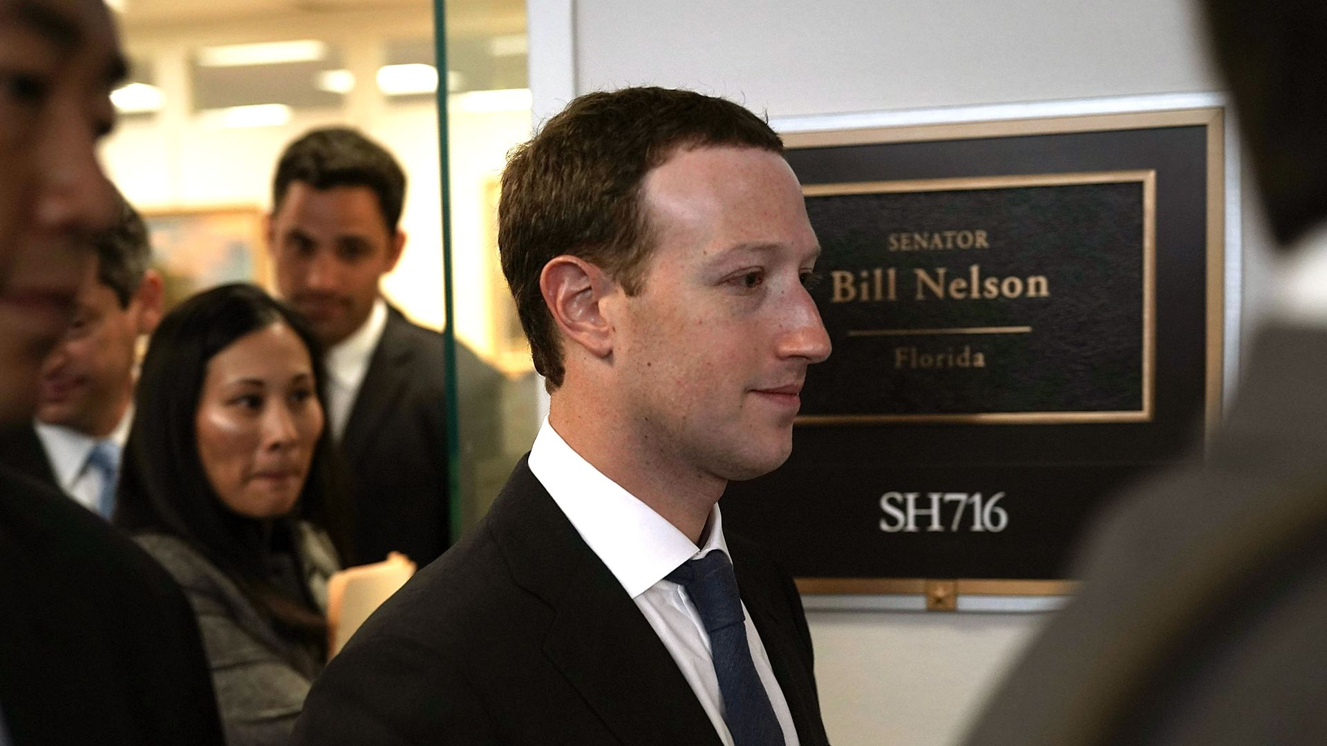 Facebook CEO Mark Zuckerberg walks by a sign for Bill Nelson's office