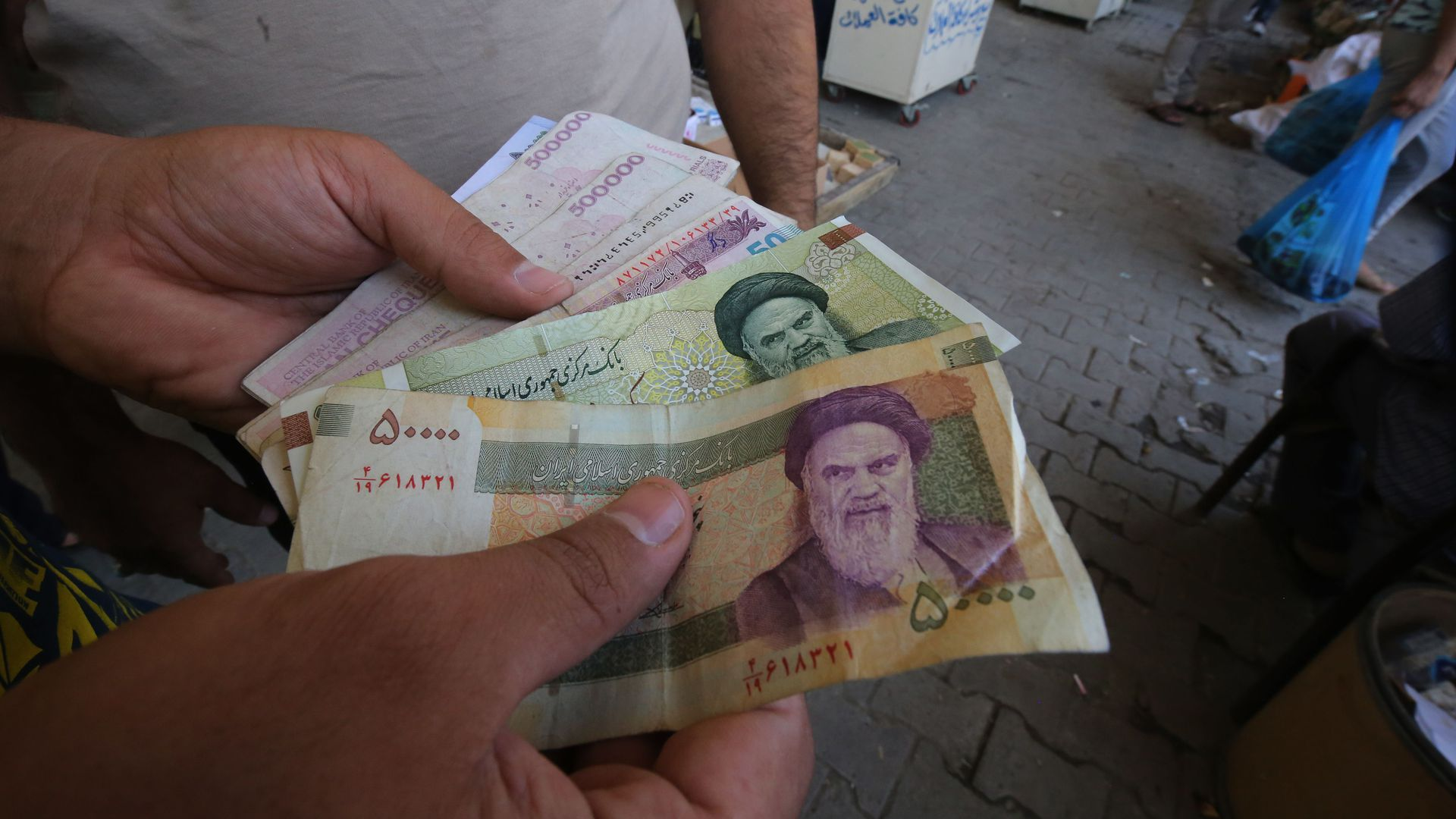An Iraqi peddler holds in his hand banknotes of Iranian rials for exchange in the Iraqi capital Baghdad.
