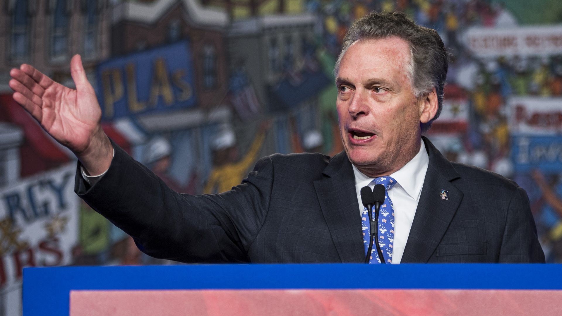 In this image, McAuliffe stands and gestures at a podium while speaking.