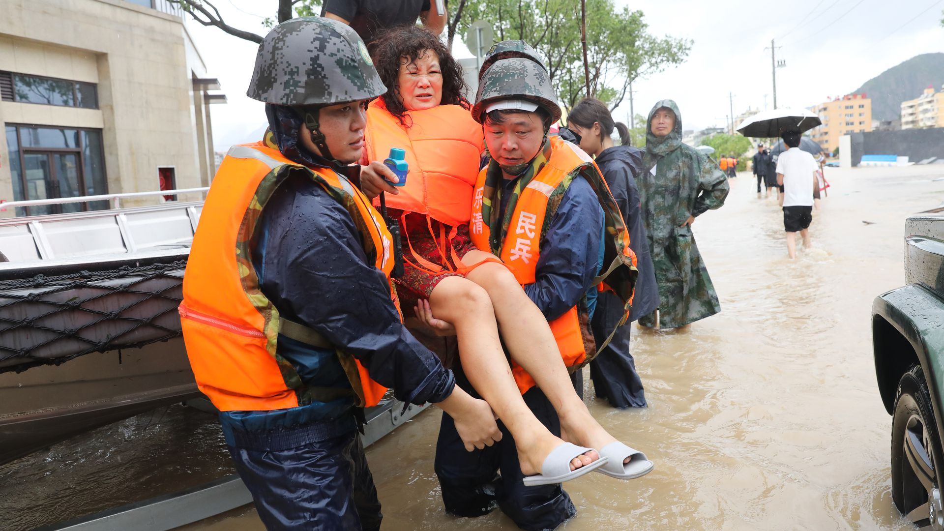 Rescuers evacuate an injured woman as Typhoon Lekima brings heavy rain and strong wind at Dajing Town on August 10