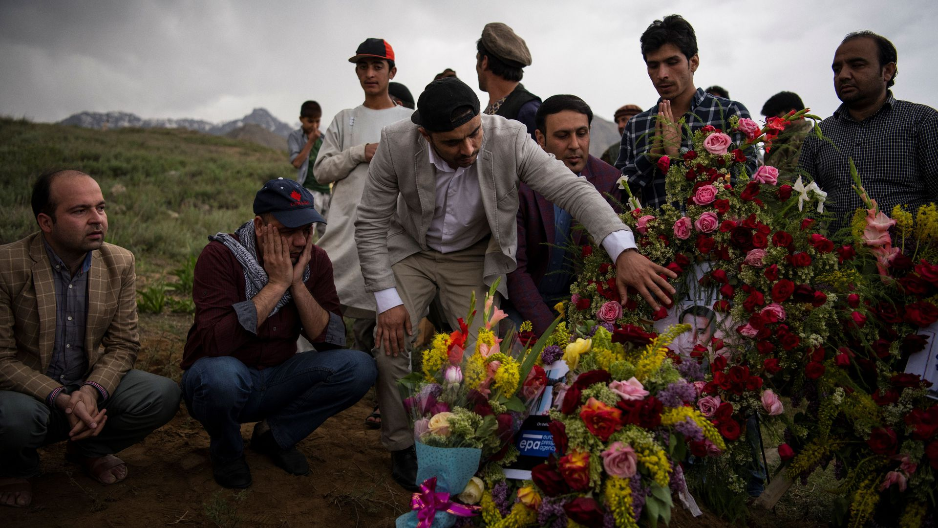 Friends and relatives of Agence France Presse Afghanistan Chief Photographer Shah Marai Faizi gather at his burial in Gul Dara, Kabul on April 30, 2018.